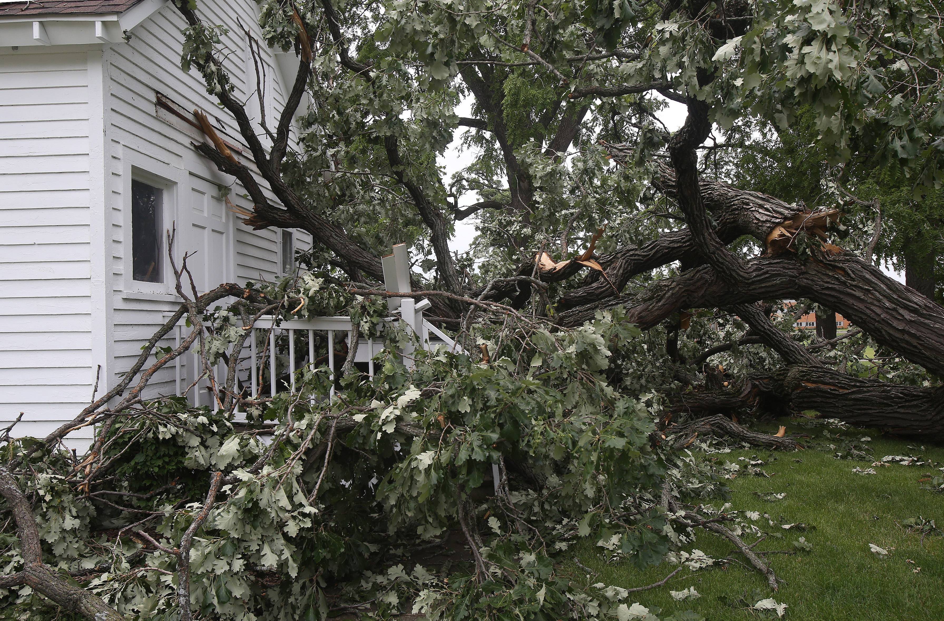 The back porch of the historic Andrew C. Cook House in Wauconda is damaged by a tree that fell during a storm Saturday afternoon.