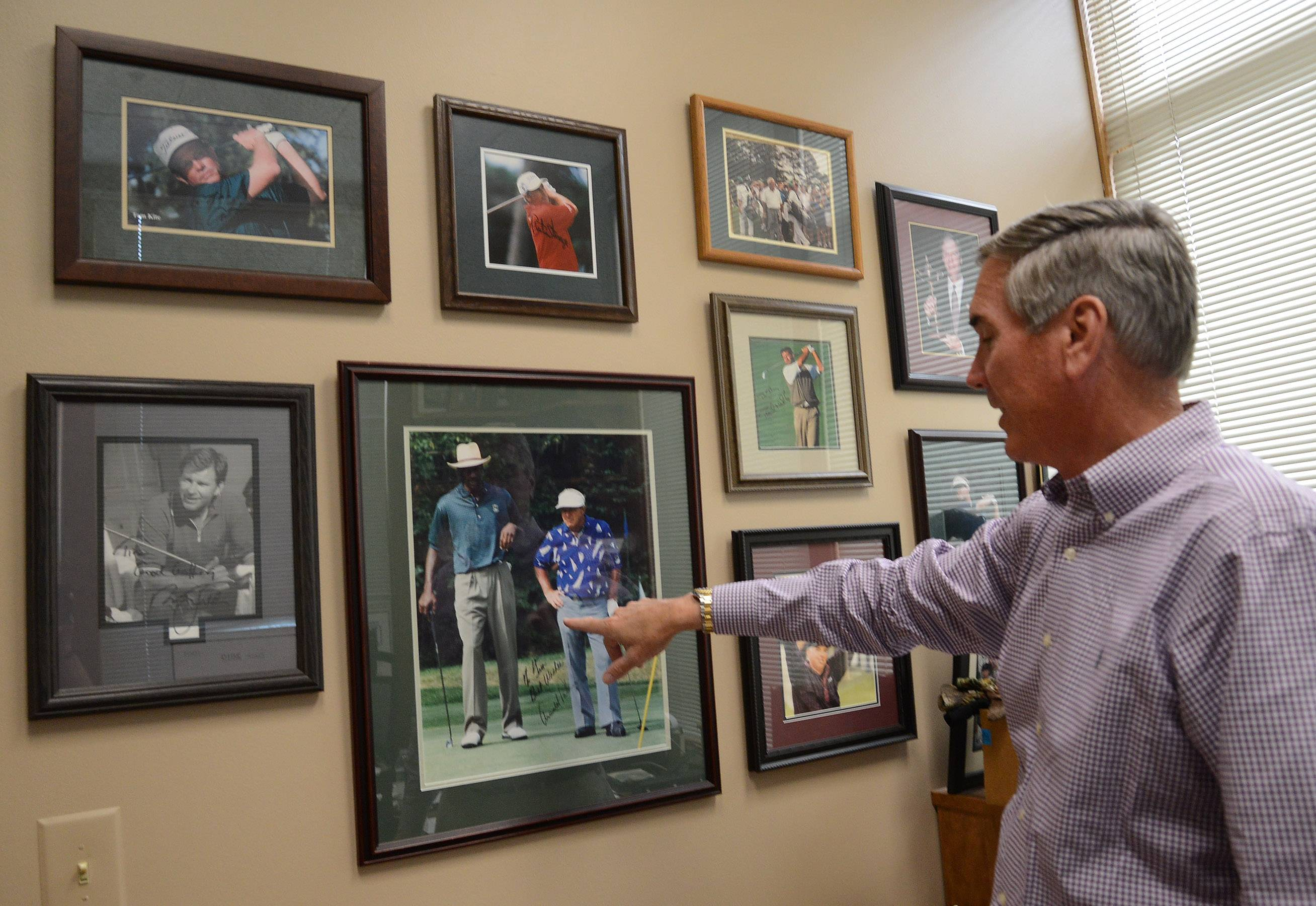 New Illinois Republican Party chairman and Cook County Commissioner Tim Schneider looks over his autographed pictures of famous golfers at the Golf Club of Illinois in Algonquin, which he owns.