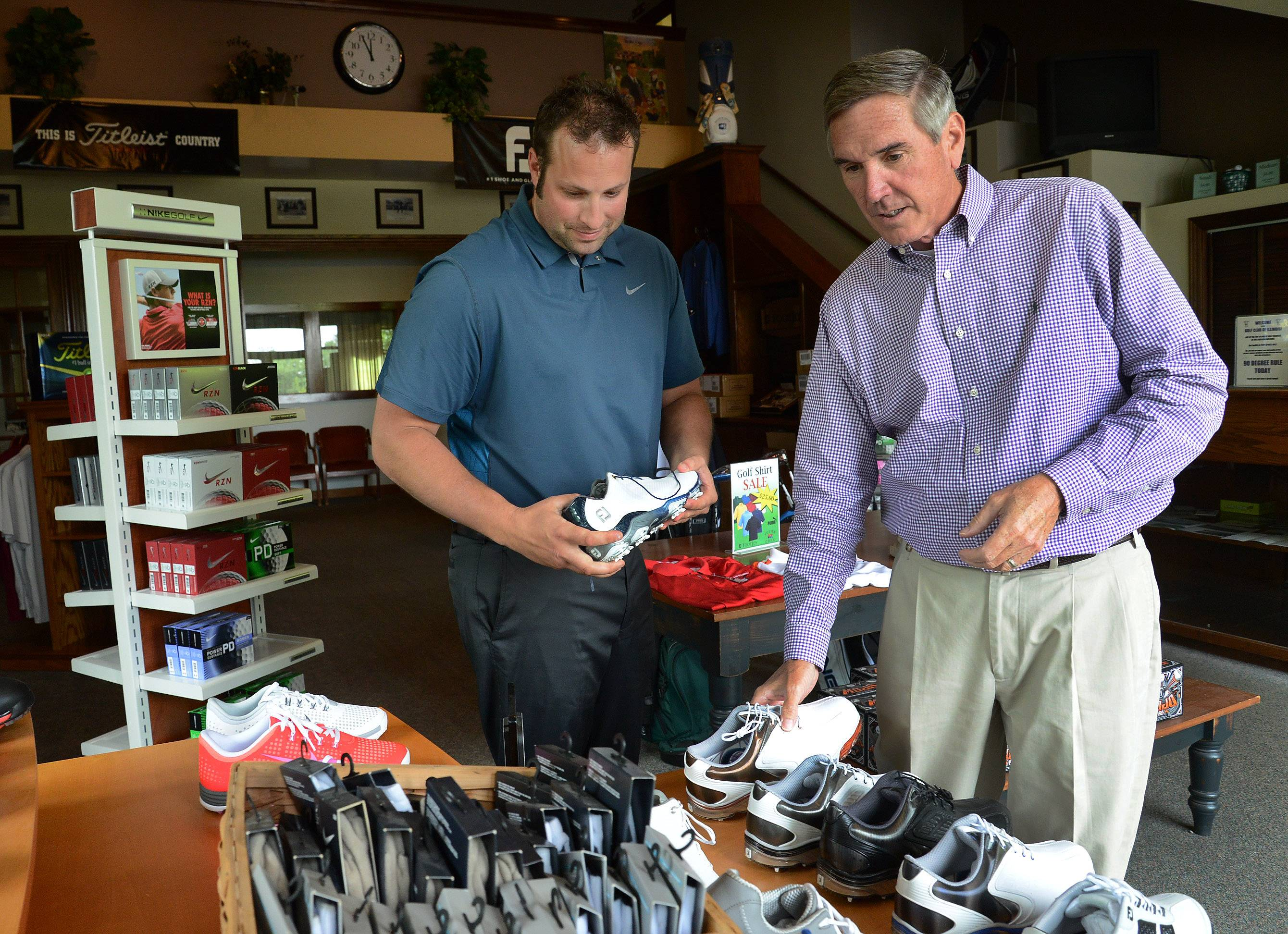New Illinois Republican Party chairman and Cook County Commissioner Tim Schneider visits the pro shop with Assistant General Manager Robert Lemke at the Golf Club of Illinois, which Schneider owns.