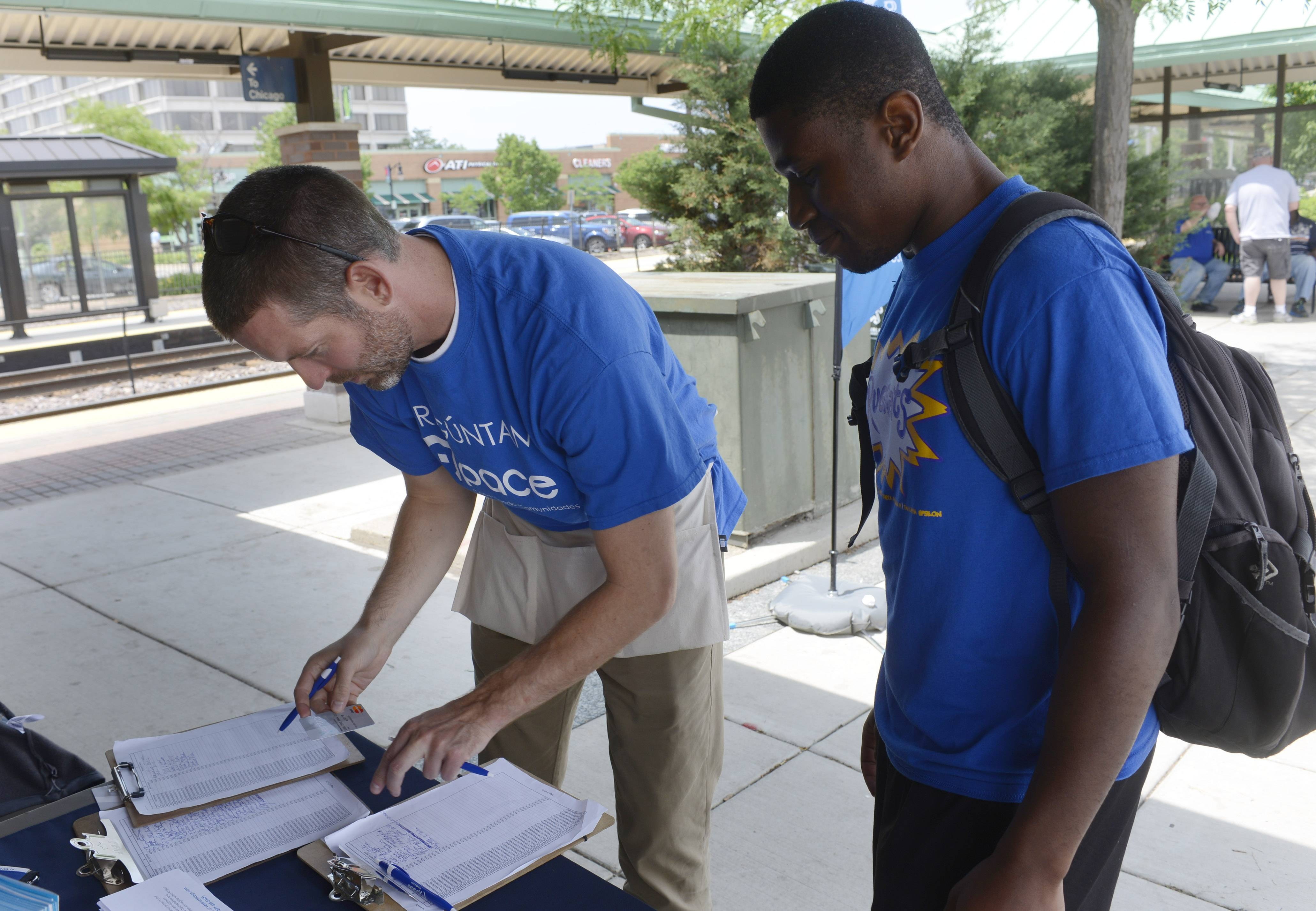 Pace representative Colin Fleming, left, signs up Brandyn Gray of Prospect Heights for the new Ventra fare system at the Des Plaines Metra station Thursday.