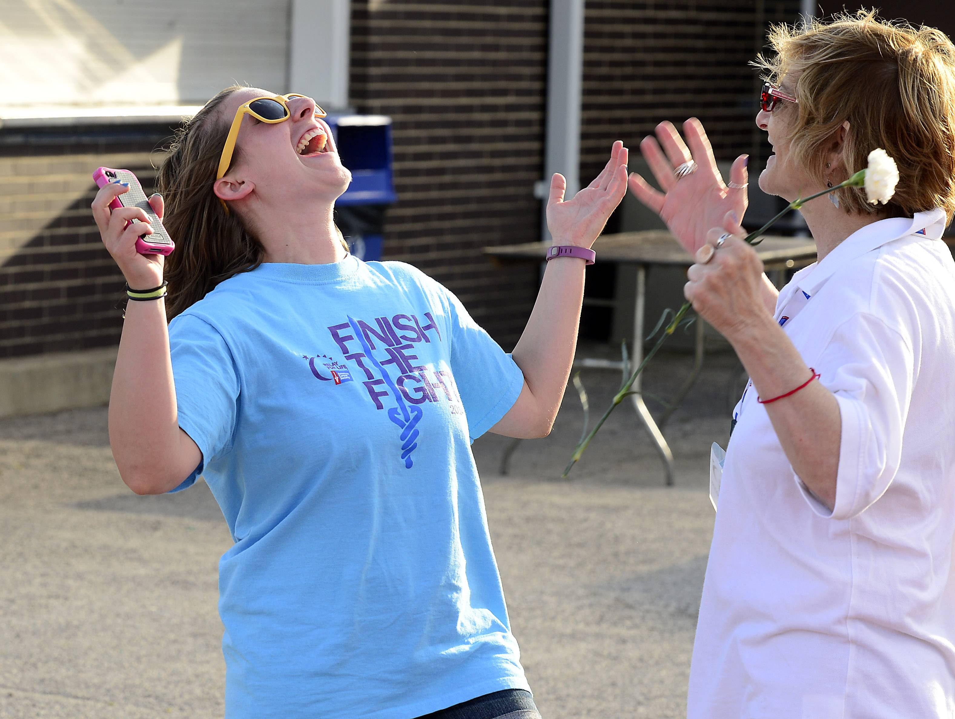 Volunteer Becca Urban, 24, of Arlington Heights, left, and staff personal for the American Cancer Society Susan Grossman, of Arlington Heights, come together to celebrate life at the annual Relay for Life against Cancer event at Hersey High School on Friday.