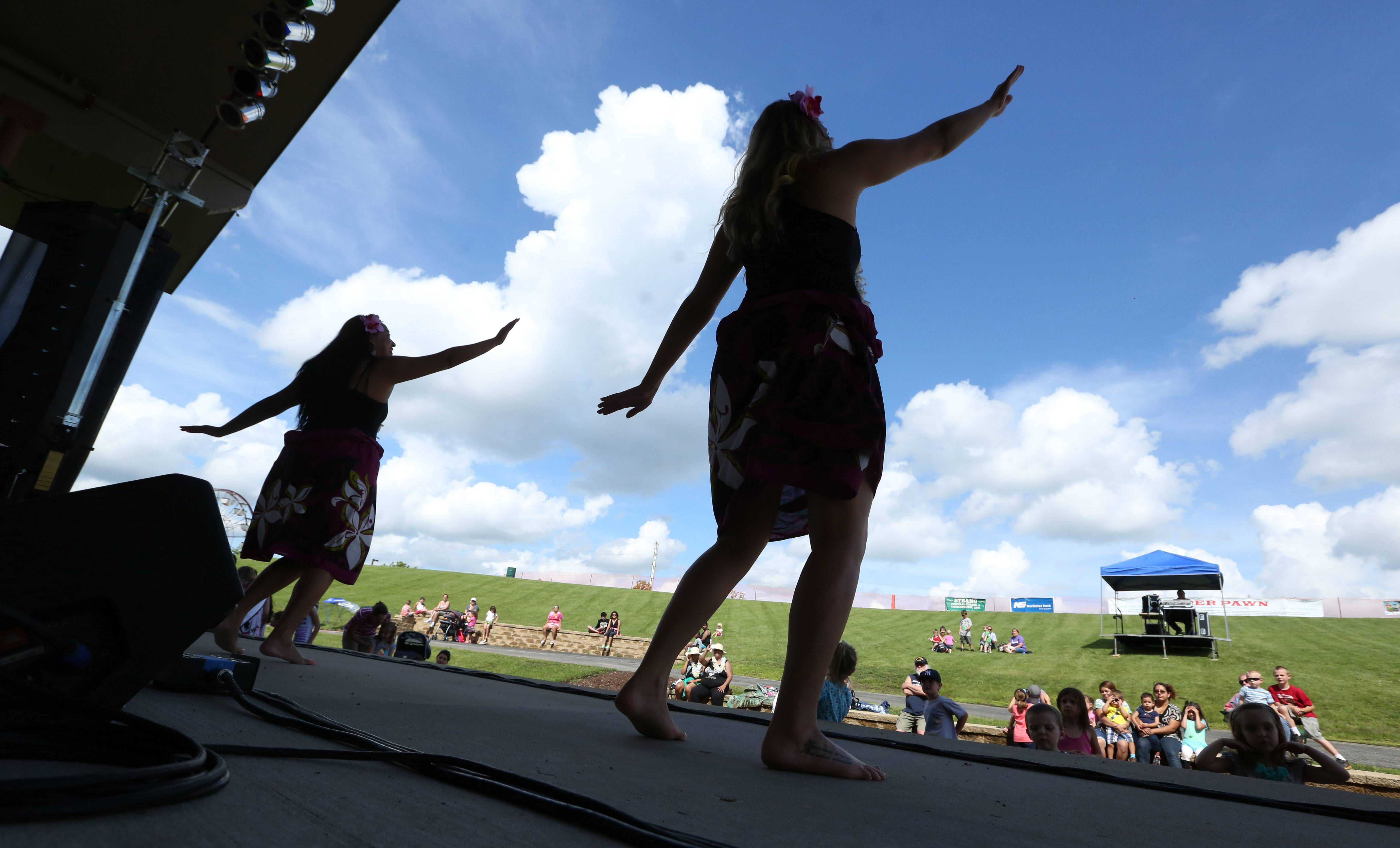 Christina Baske, of Des Plaines, right, and Kathryn Tobias, of Chicago, both with Barefoot Hawaiian in Des Plaines, perform a Polynesian dance at BeachFest on Friday in Round Lake Beach.