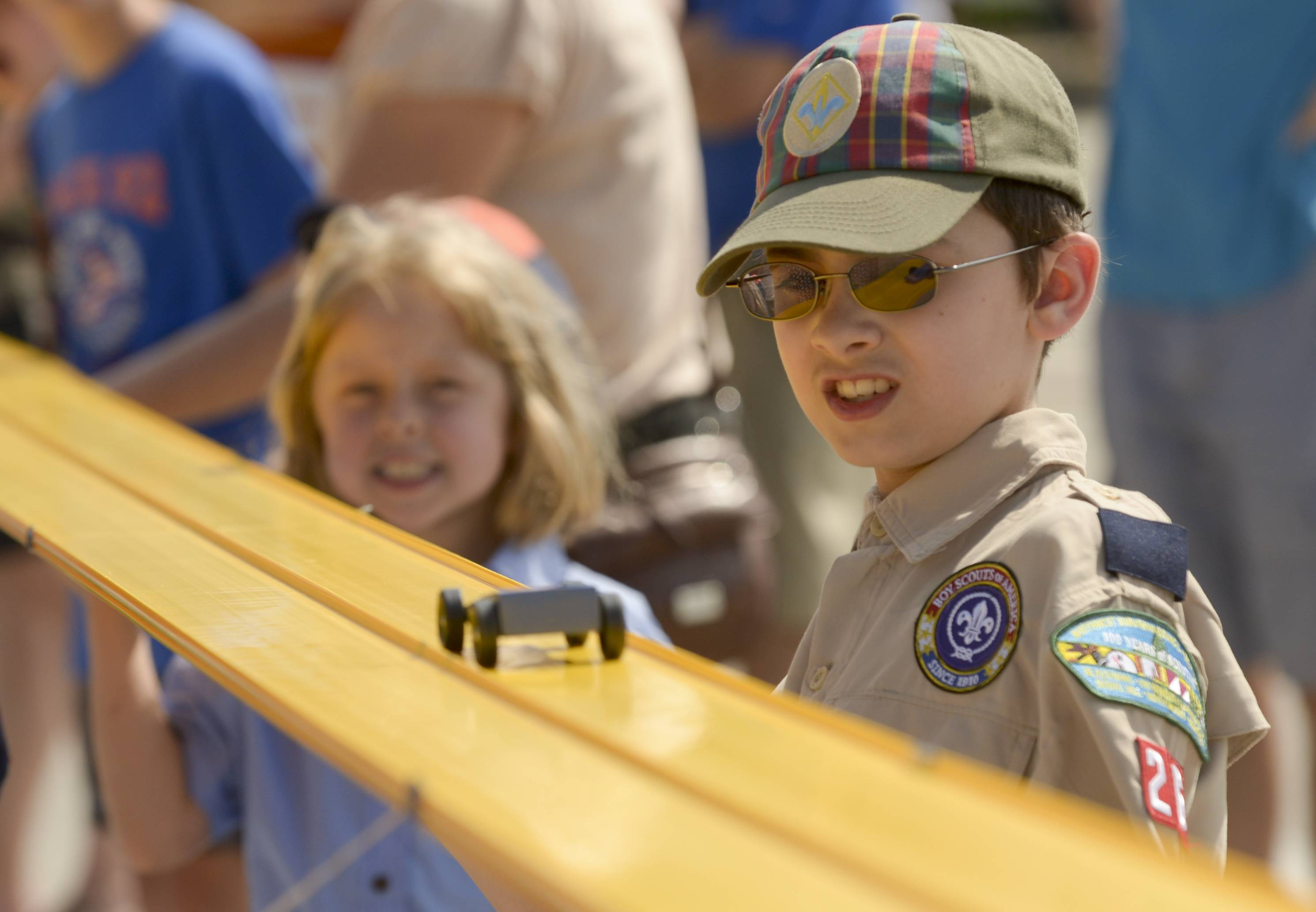 Will Knogl, 10, of Des Plaines Pack 263, watches as one of the cars wiz past him as the Northwest Suburban Council - Boy Scouts of America successfully raced a car along a 620 foot track in parking lot G of Woodfield Mall in Schaumburg. The council hopes that this will get them into the Guinness Book of World Record for the Longest Pinewood Derby Track.