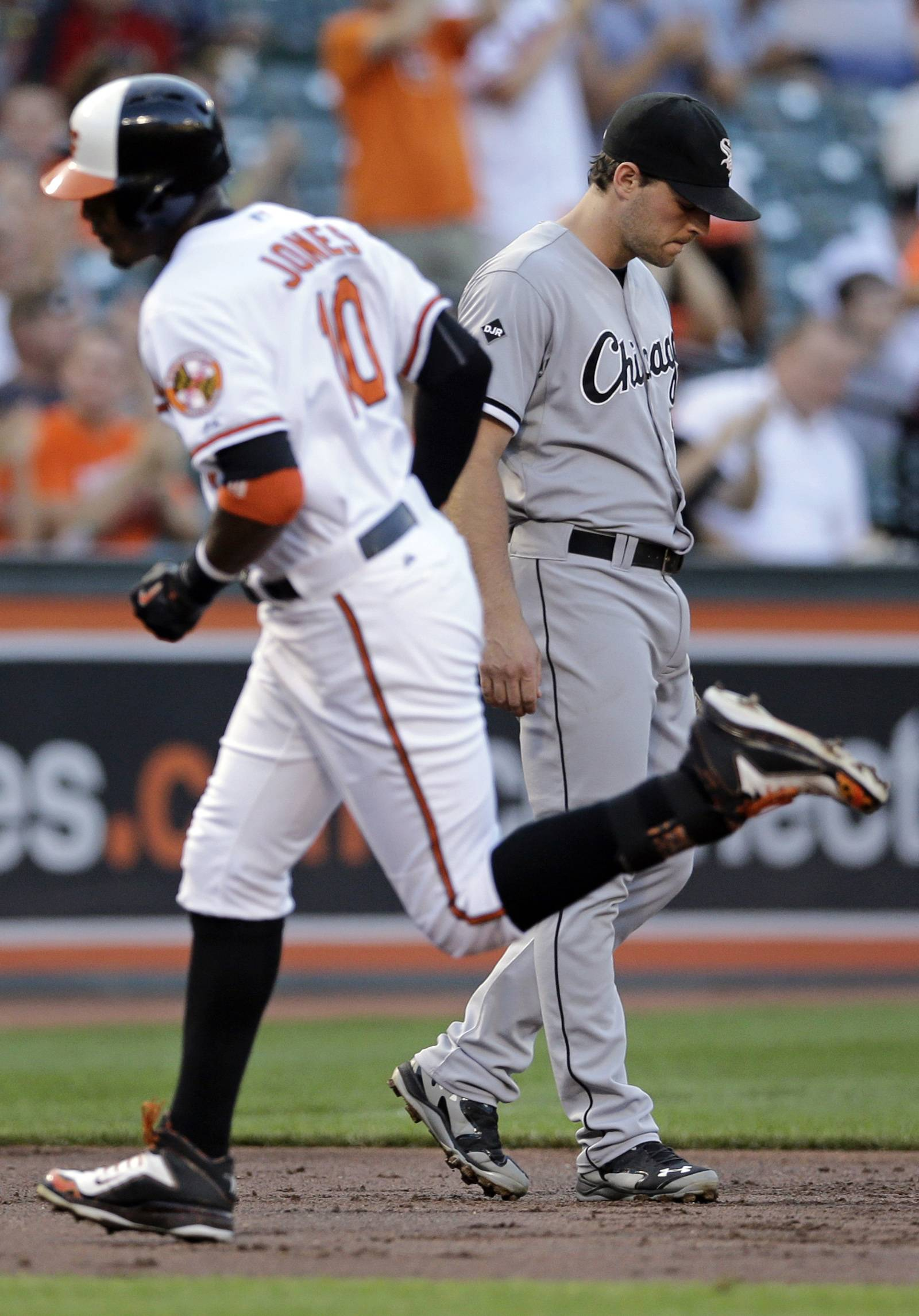 Chicago White Sox third baseman Conor Gillaspie, back right, walks in the infield as Baltimore Orioles' Adam Jones rounds the bases after hitting a two-run home run in the first inning of a baseball game Monday in Baltimore.