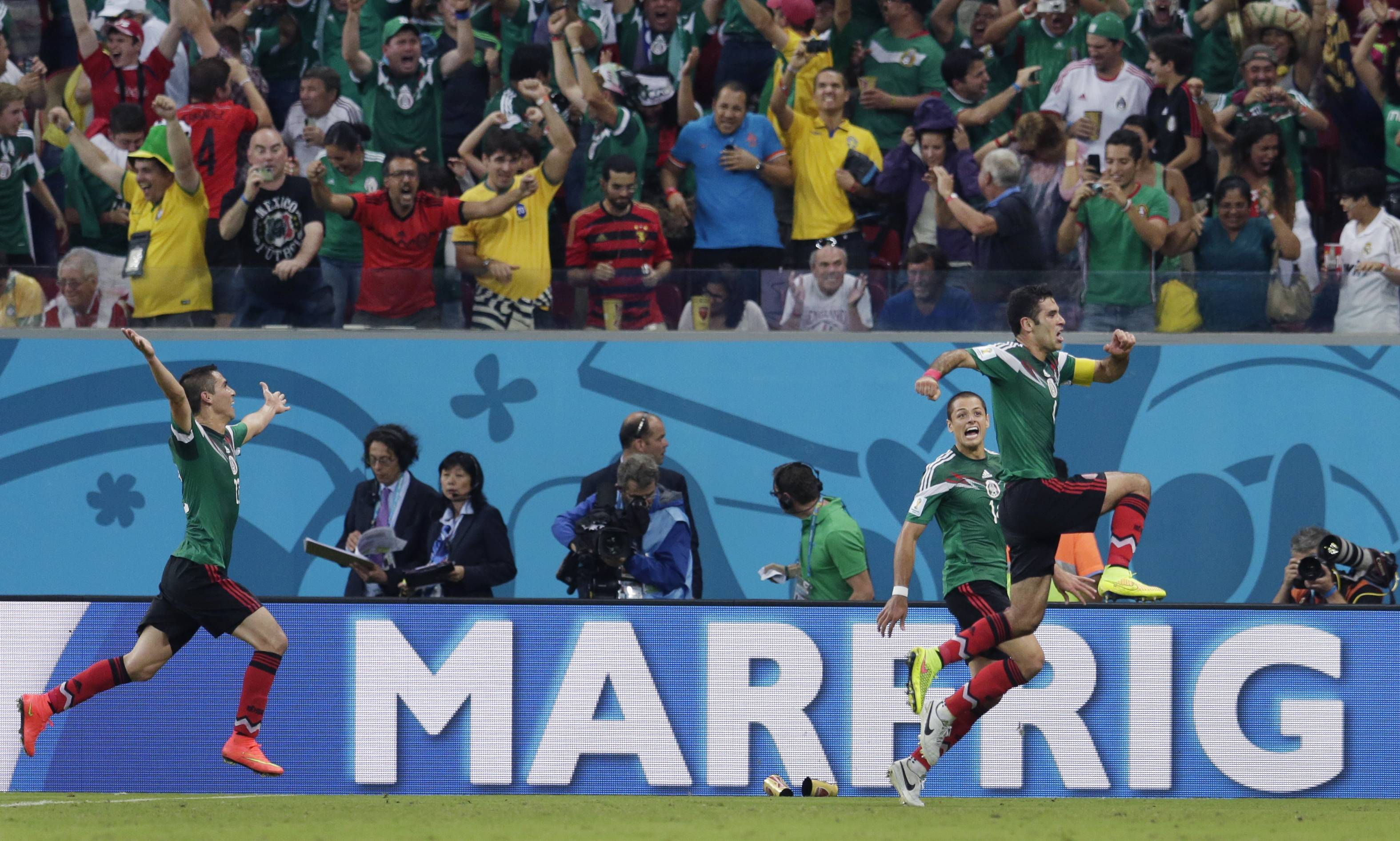 Mexico's Rafael Marquez , right, celebrates after scoring the opening goal Monday during the group A World Cup soccer match between Croatia and Mexico at the Arena Pernambuco in Recife, Brazil.