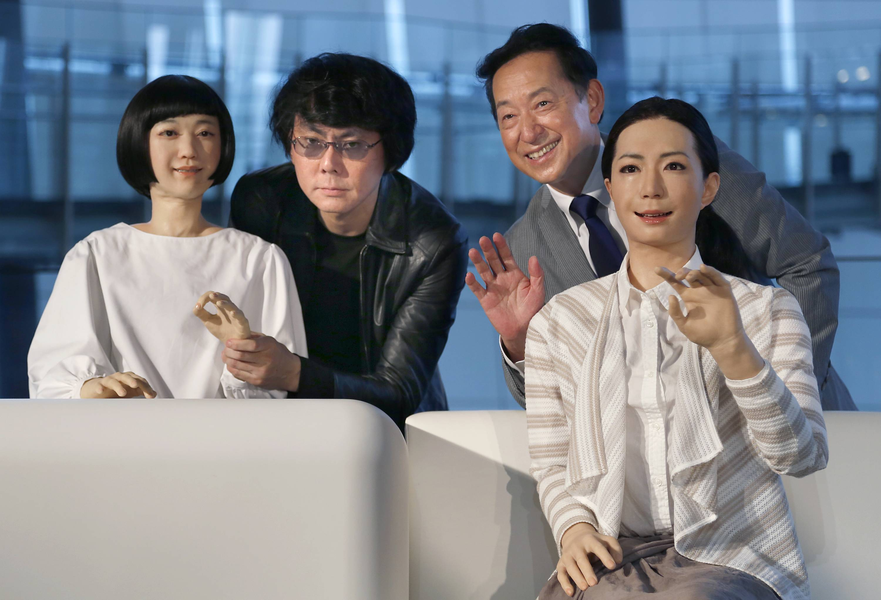 Japanese android expert Hiroshi Ishiguro, second left, and National Museum of Emerging Science and Innovation Miraikan Chief Executive Director Mamoru Mohri, second right, pose with a female-announcer robot called Otonaroid, right, and a girl robot called Kodomoroid during a demonstration of the museum's new guides in Tokyo Tuesday.