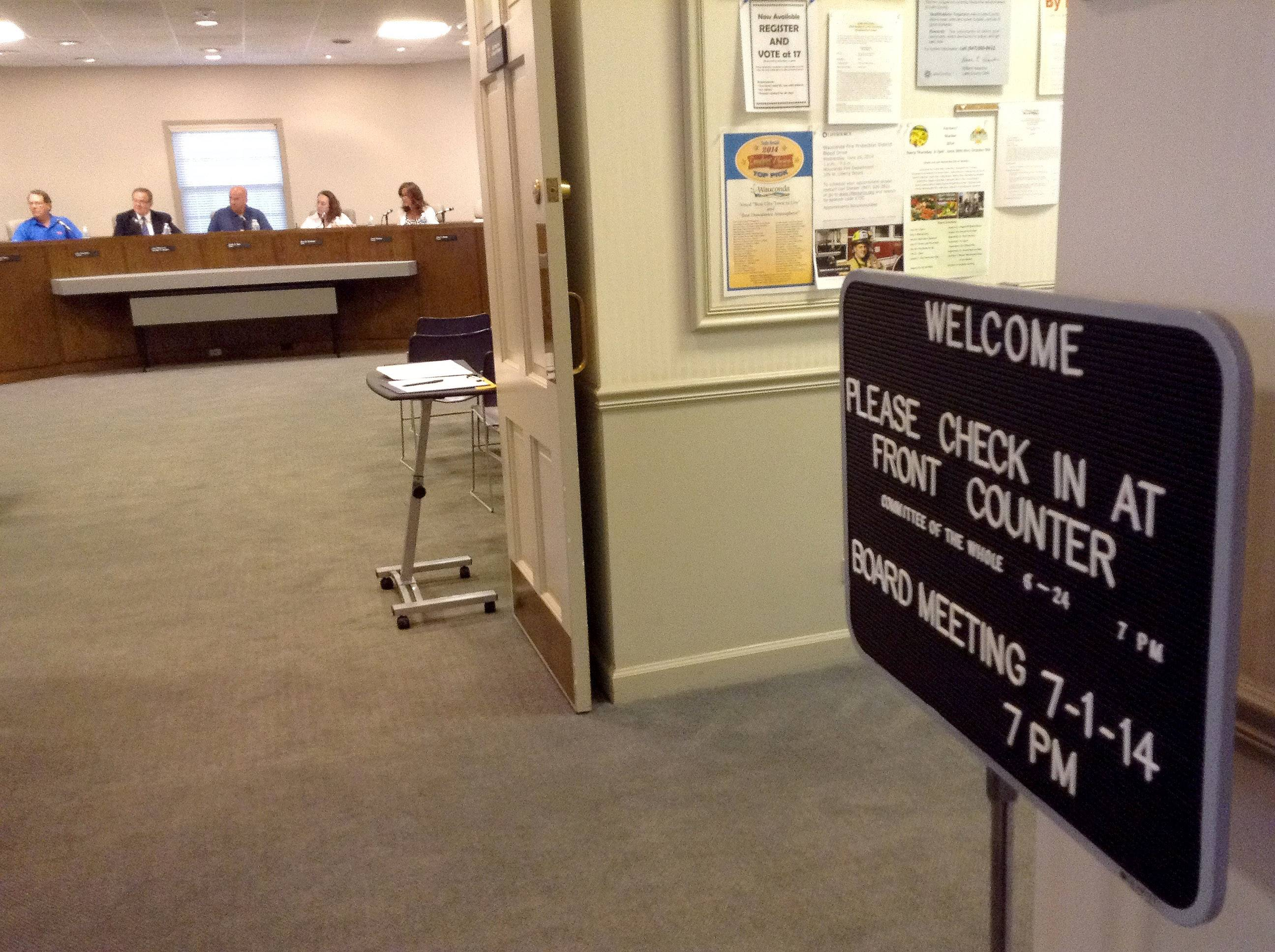 A sign in the Wauconda village hall lobby welcomes visitors as trustees meet in the boardroom.