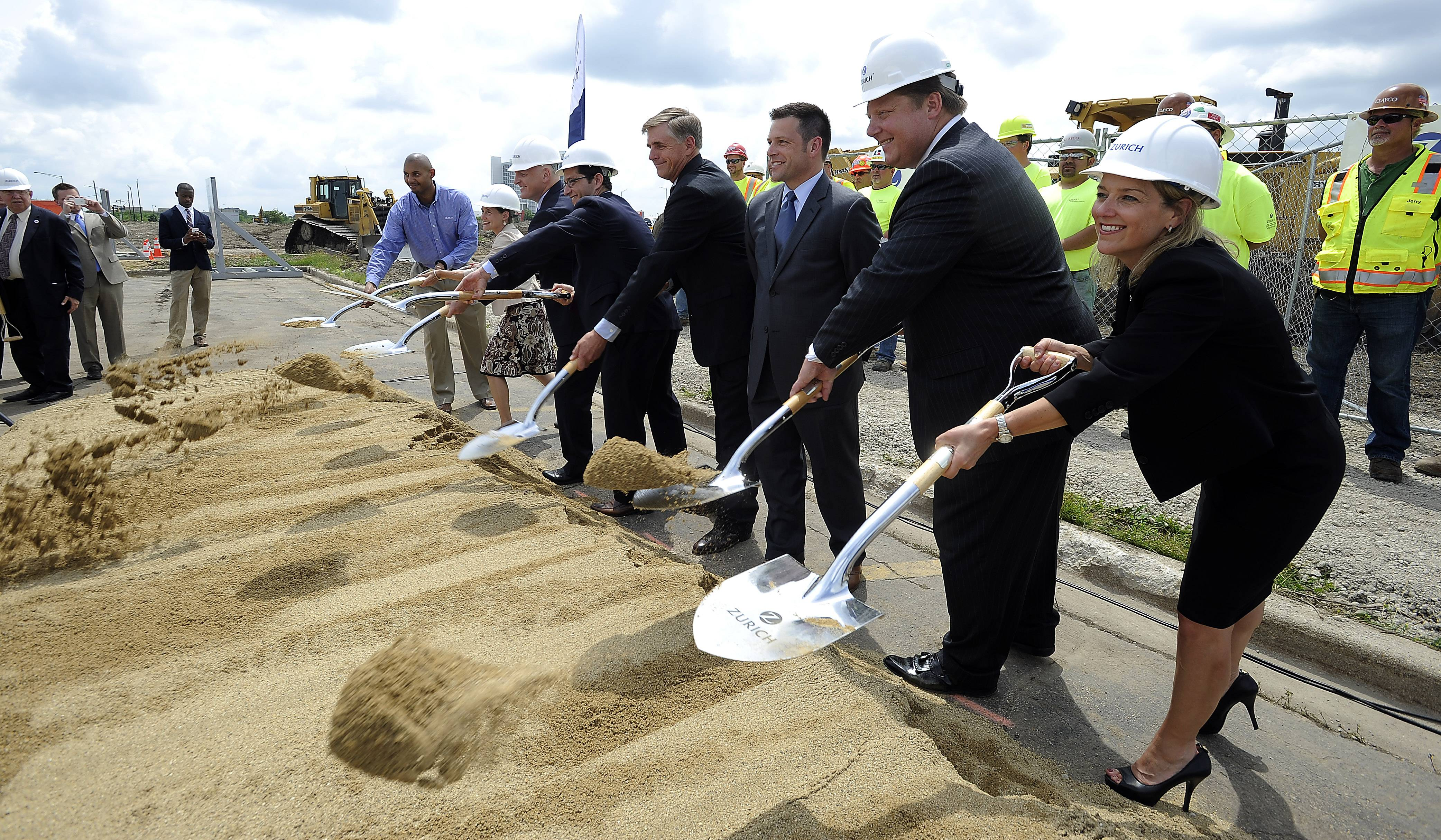 Jen Kyung, Zurich North America business lead, throws a shovel of sand at the ceremony with other dignitaries Tuesday.
