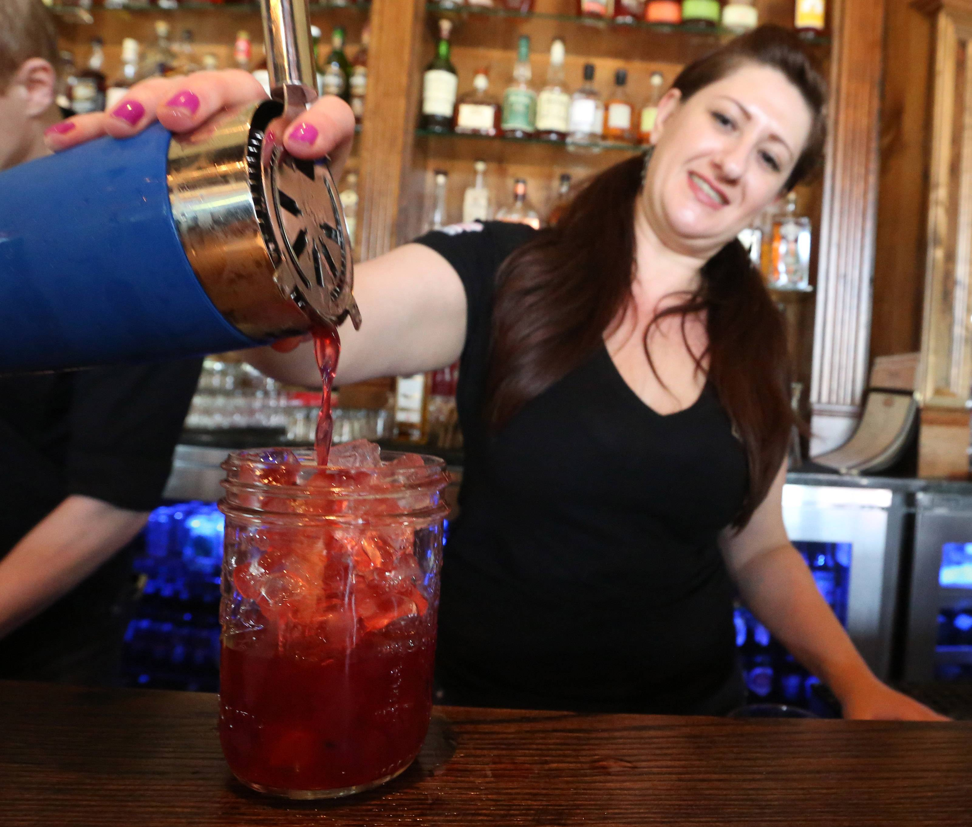 Mixologist Susan Brown pours a blackberry bourbon cocktail at Spears in Wheeling.