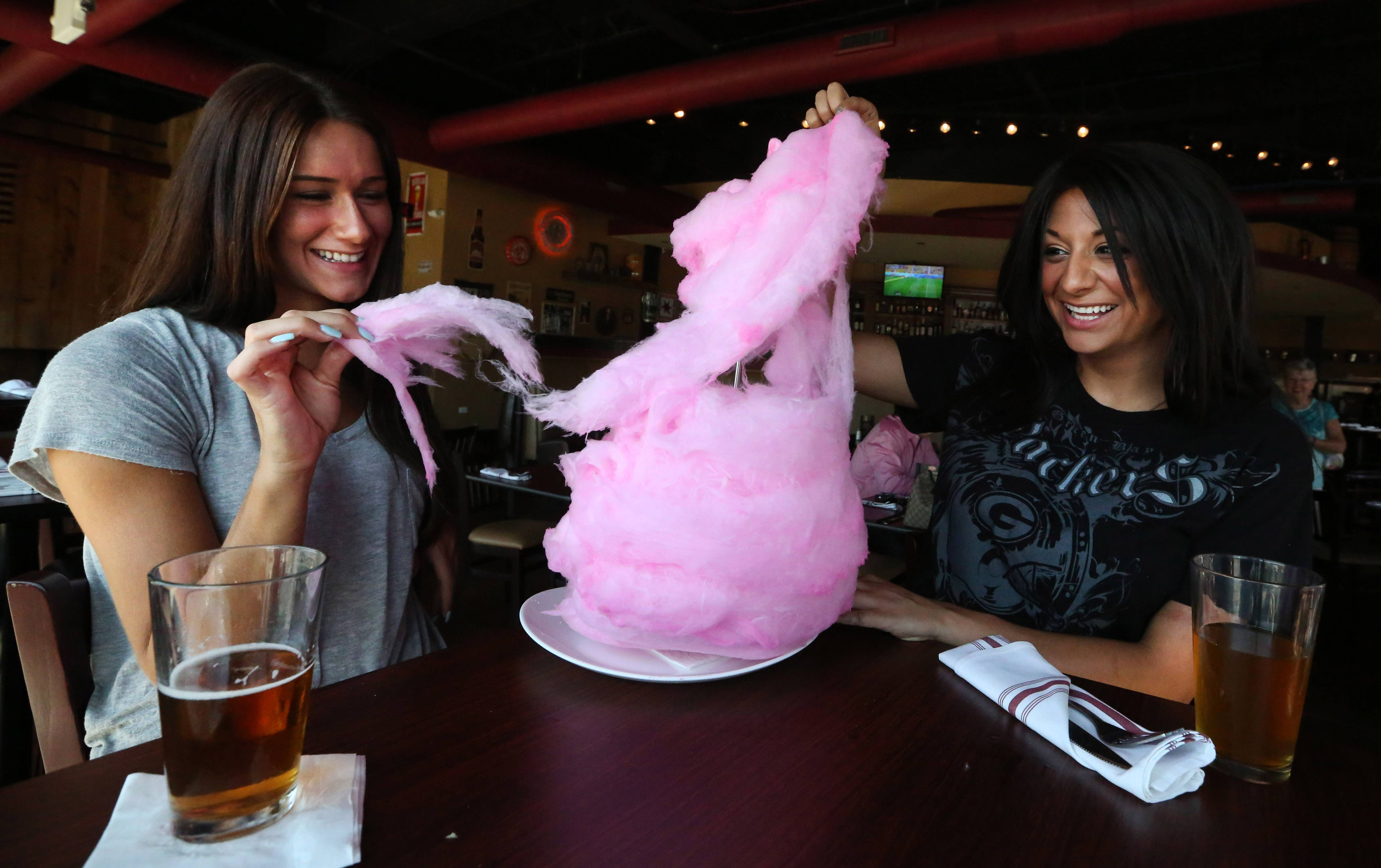 Christina Moretti, left, of Rolling Meadows and Mioara Alfano of Wheeling try cotton candy at Spears in Wheeling.