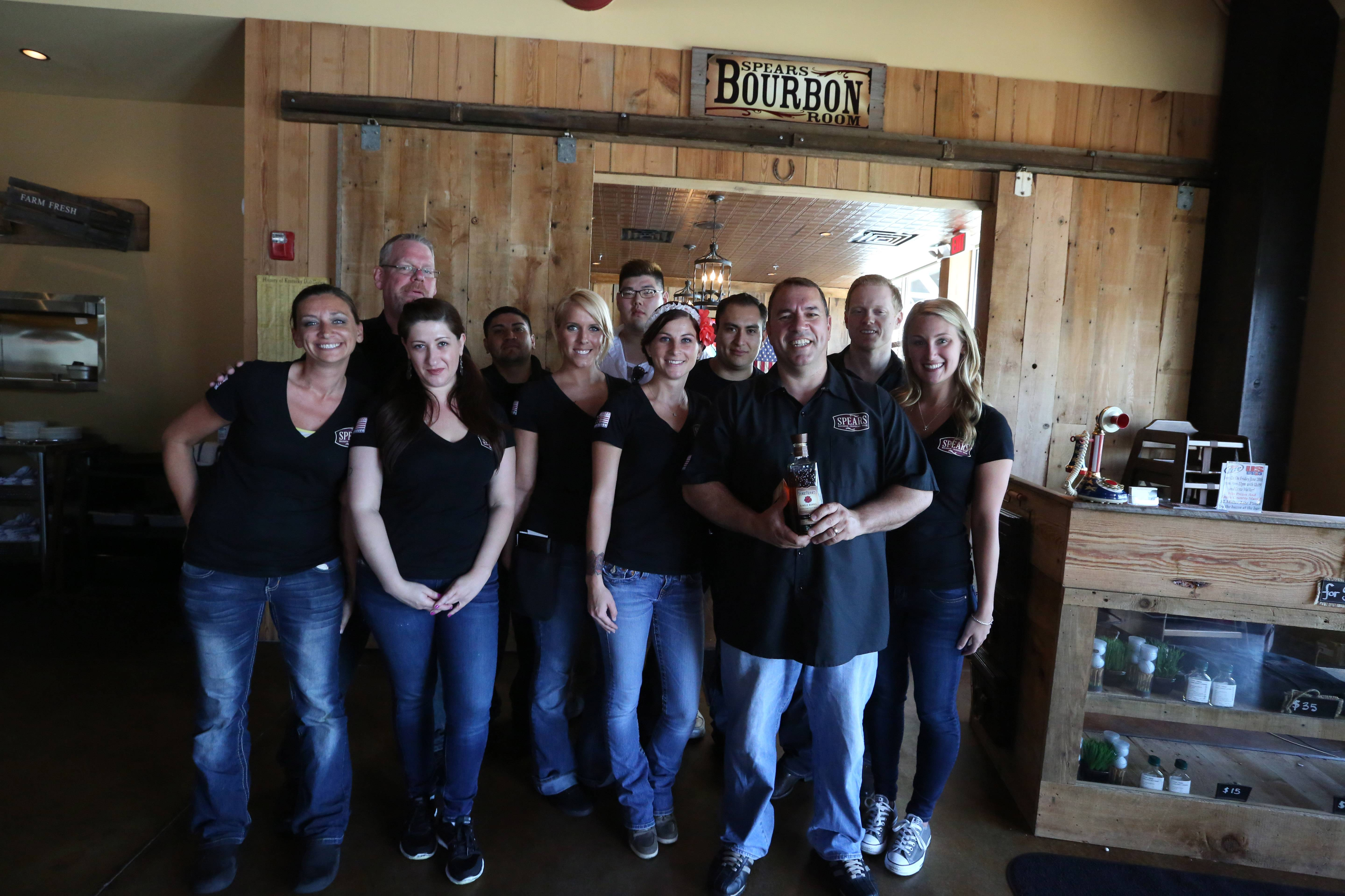 Owner Joe Romeo, holding bottle, shows off his crew at Spears in Wheeling. The eatery showcases burgers bourbon and beer.