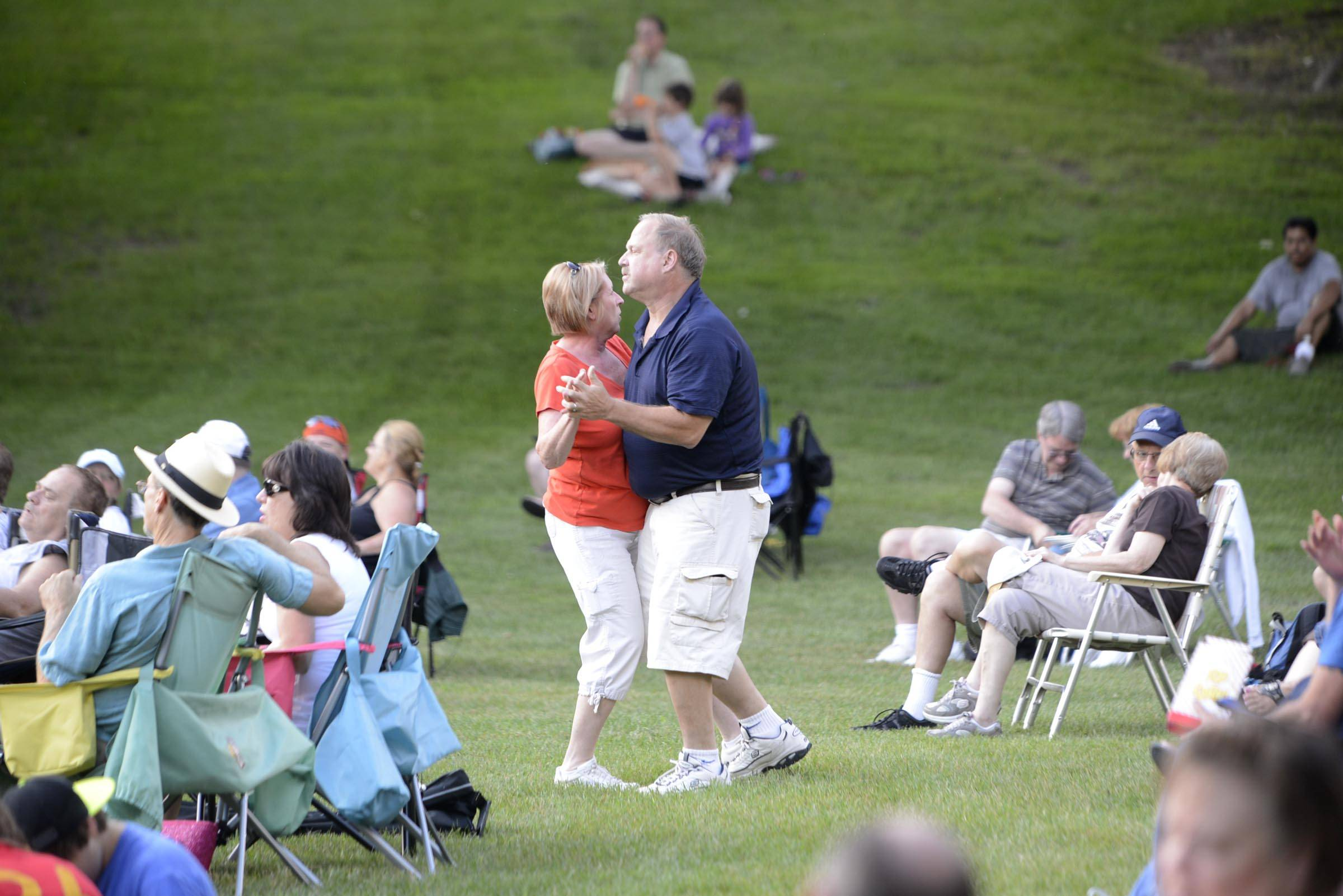 John and Dottie Schmitz of South Elgin dance among the crowd Tuesday in Wing Park while the R Gang band performs as part of the Elgin Concerts in the Park program.