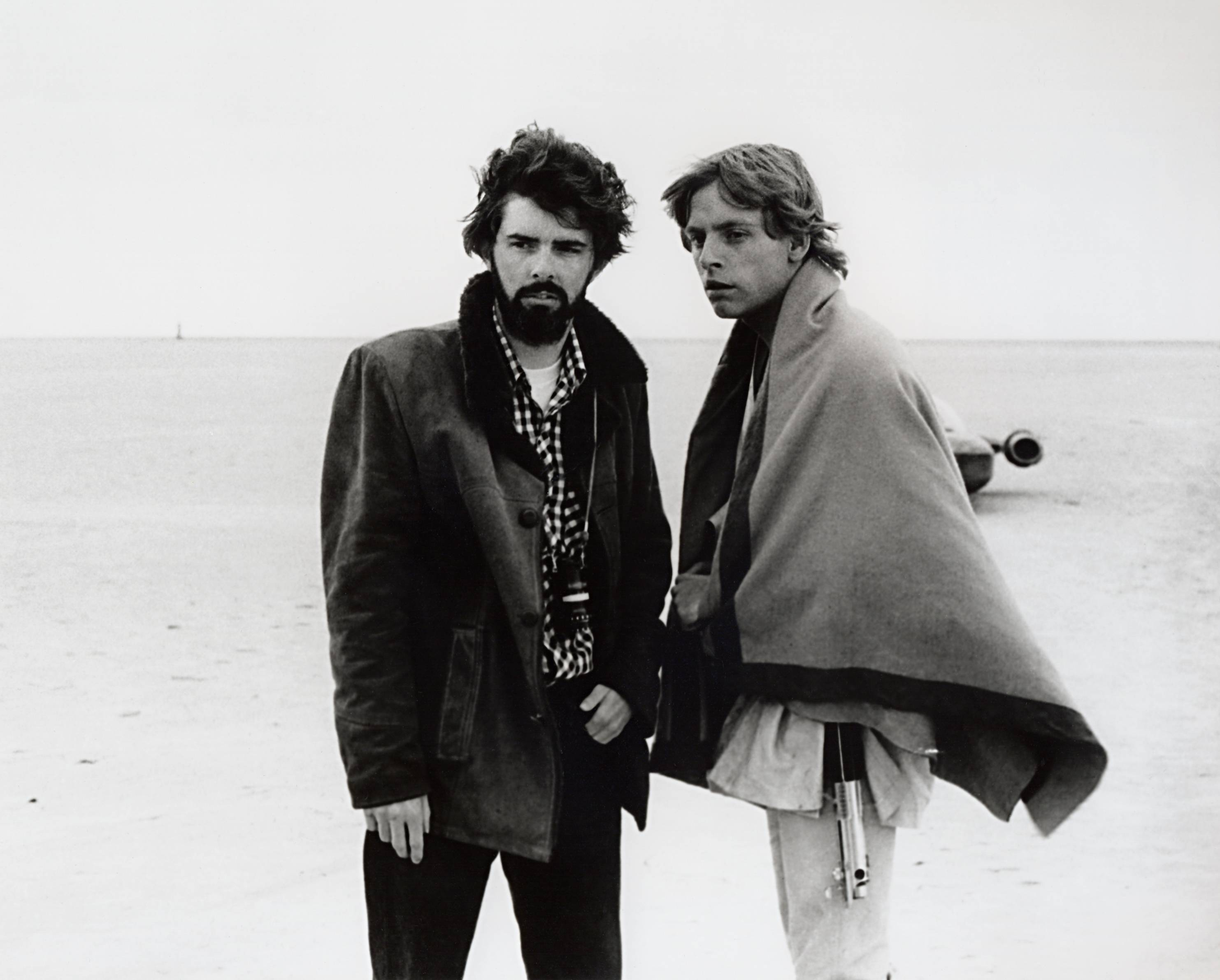 "Director George Lucas and actor Mark Hamill confer on the salt flats of Tunisia during principal photography for the original ""Star Wars"" in 1976."