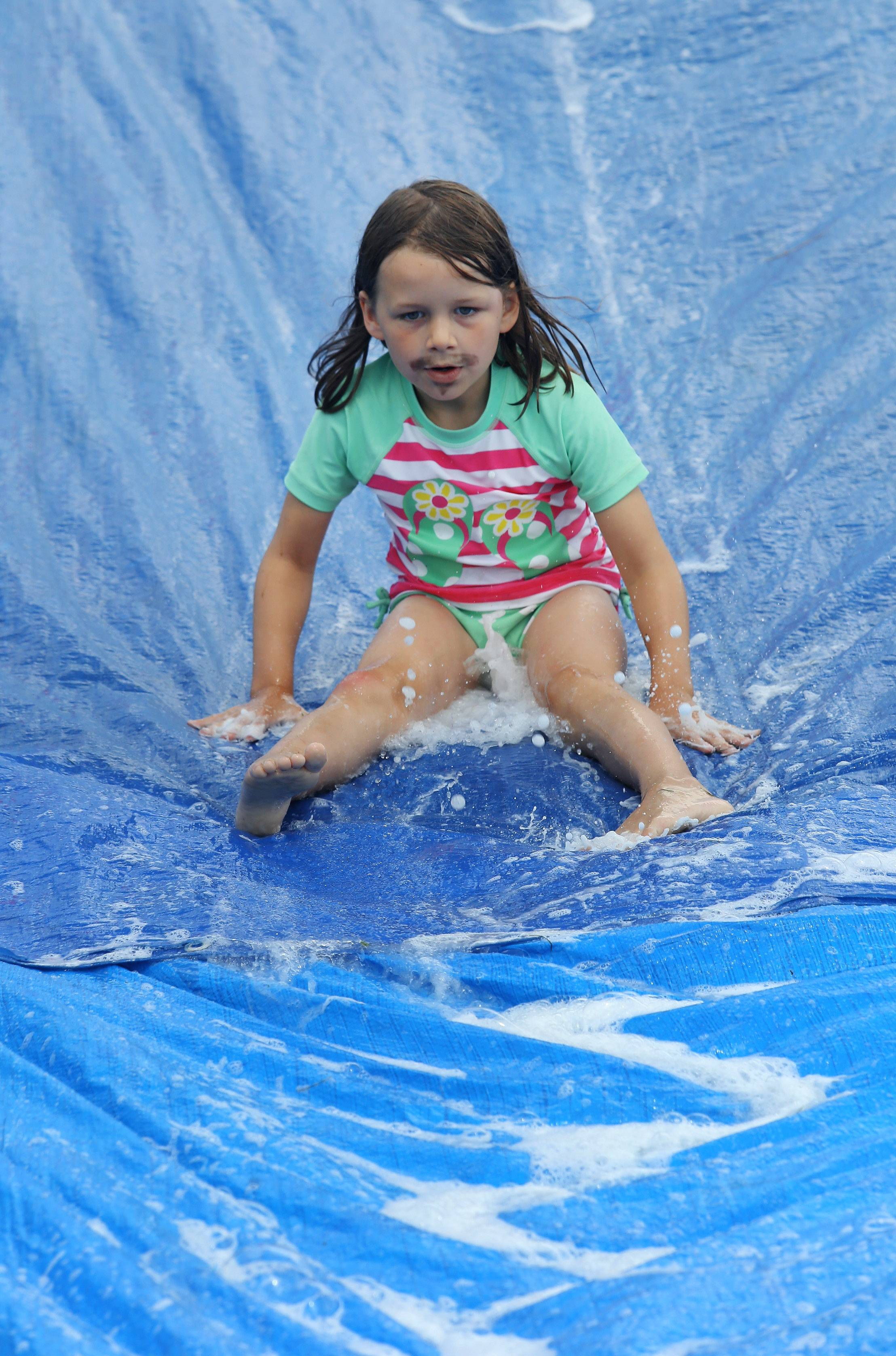 "Lucy Van Brundt, 6, of Libertyville goes down a water slide Tuesday during Wet Day at the Spotlight Youth Theater summer camp at The Chapel in Libertyville. The weeklong camp focuses on voice, drama and dance as children prepare for Friday's presentation of ""Surfin' the High Seas."""