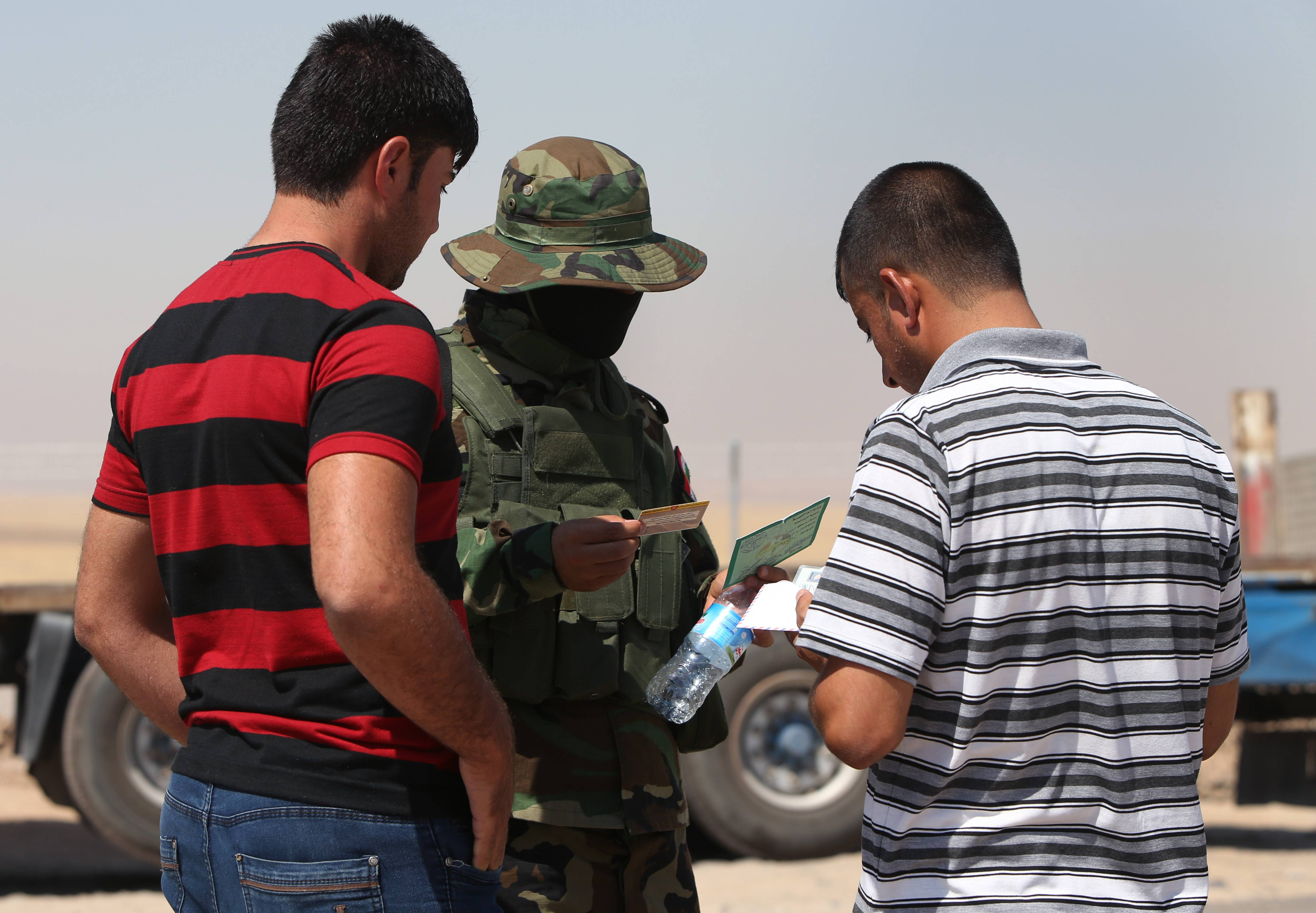 "A Kurdish security soldier checks the identity cards of Iraqi citizens at a check point Tuesday on a highway between the Iraqi city of Mosul and the Kurdish city of Irbil, in Khazer area northern Iraq. The president of Iraq's ethnic Kurdish region declared Tuesday that ""we are facing a new reality and a new Iraq"" as the country considers new leadership for its Shiite-led government as an immediate step to curb a Sunni insurgent rampage."