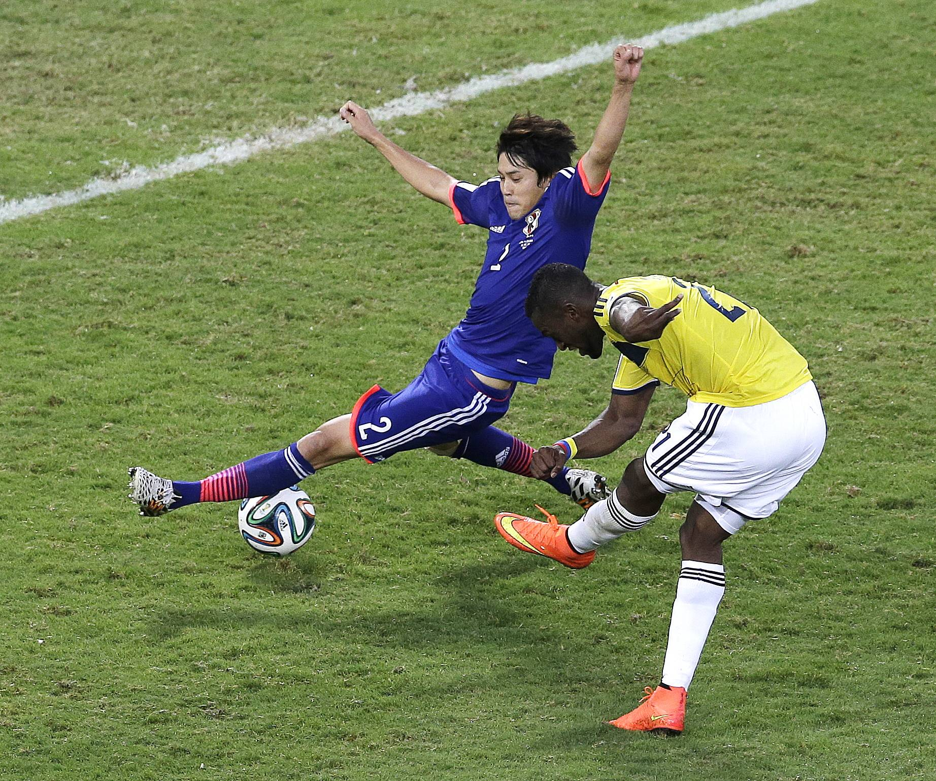 Colombia forward Jackson Martinez, right, scores past Japan defender Atsuto Uchida during the second half of a group C World Cup soccer match at the Arena Pantanal in Cuiaba, Brazil, Tuesday, June 24, 2014.