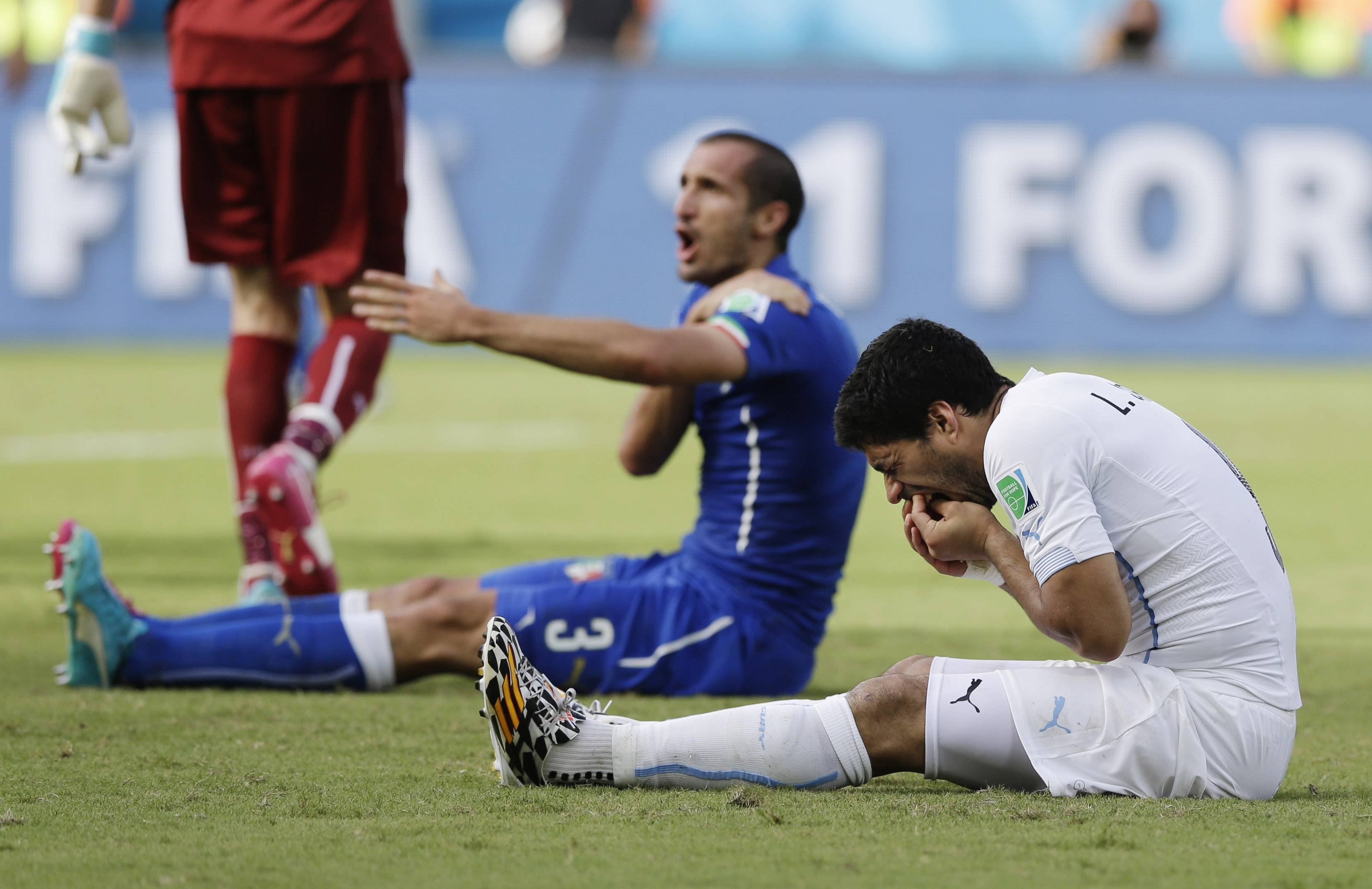 Italy's Giorgio Chiellini complains after Uruguay's Luis Suarez ran into his shoulder with his teeth Tuesday during a Group D World Cup match at the Arena das Dunas in Natal, Brazil.