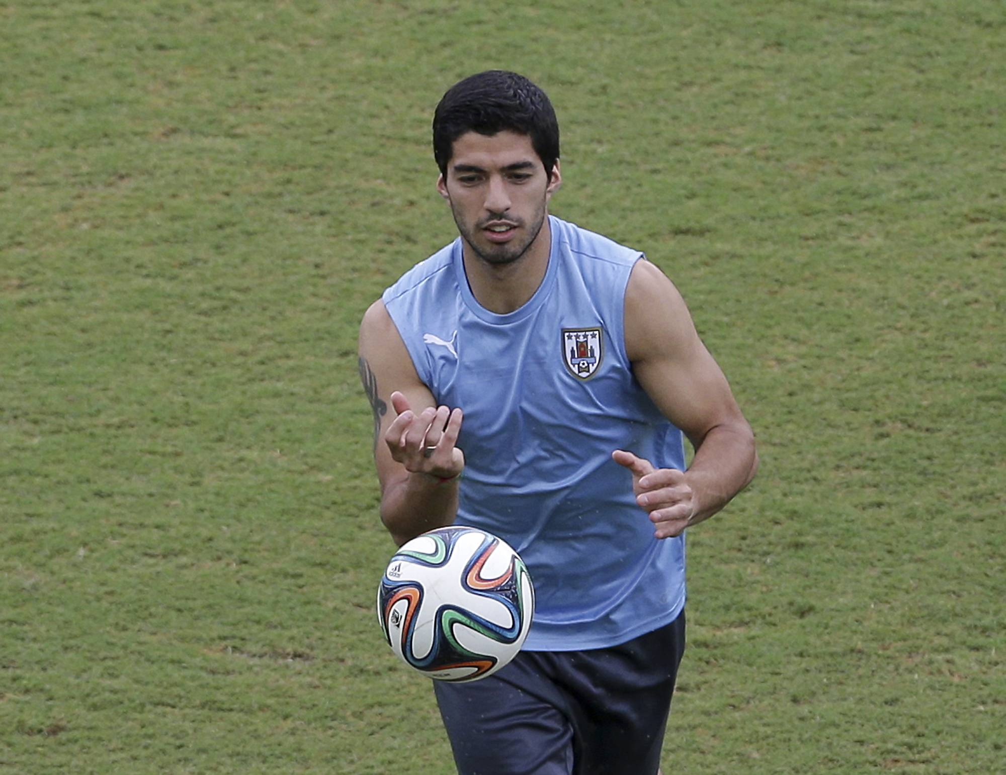 Uruguay's Luis Suarez runs on the pitch during a training session Monday. The highlight of Tuesday's matches is Italy's game against Uruguay, a contest between two former world champions that will see the winner go through to the second round.