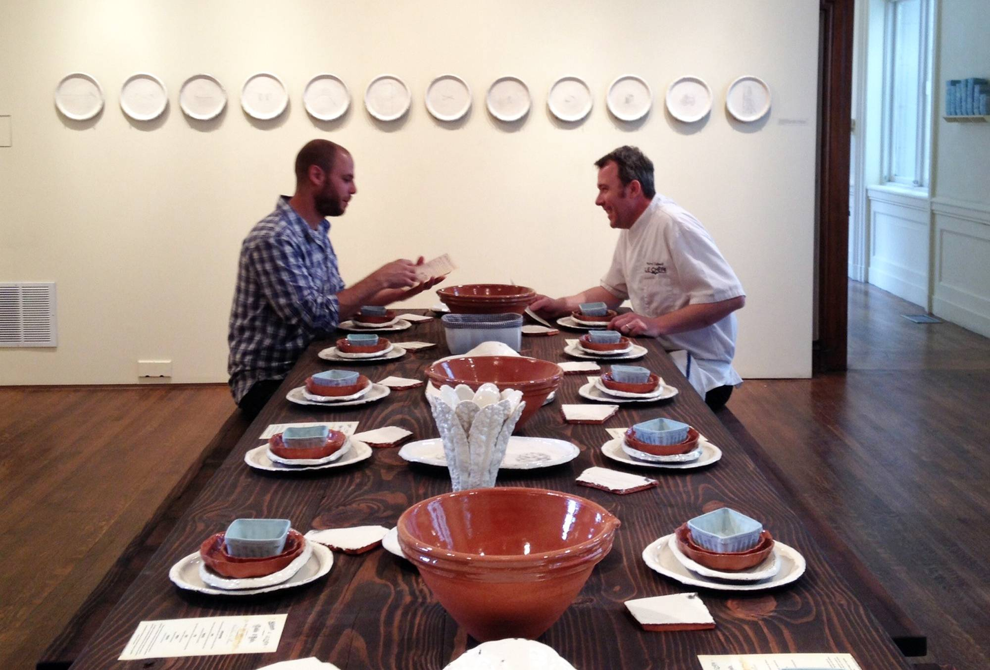 "Artist Gregg Moore, left, and chef Pierre Calmels sit at a table set with Moore's fine ceramic pottery for a show called ""Heirloom"" in Philadelphia. Calmels serves a seven-course, $150 dinner called ""Table d'Hote"" at the museum using Moore's pottery."