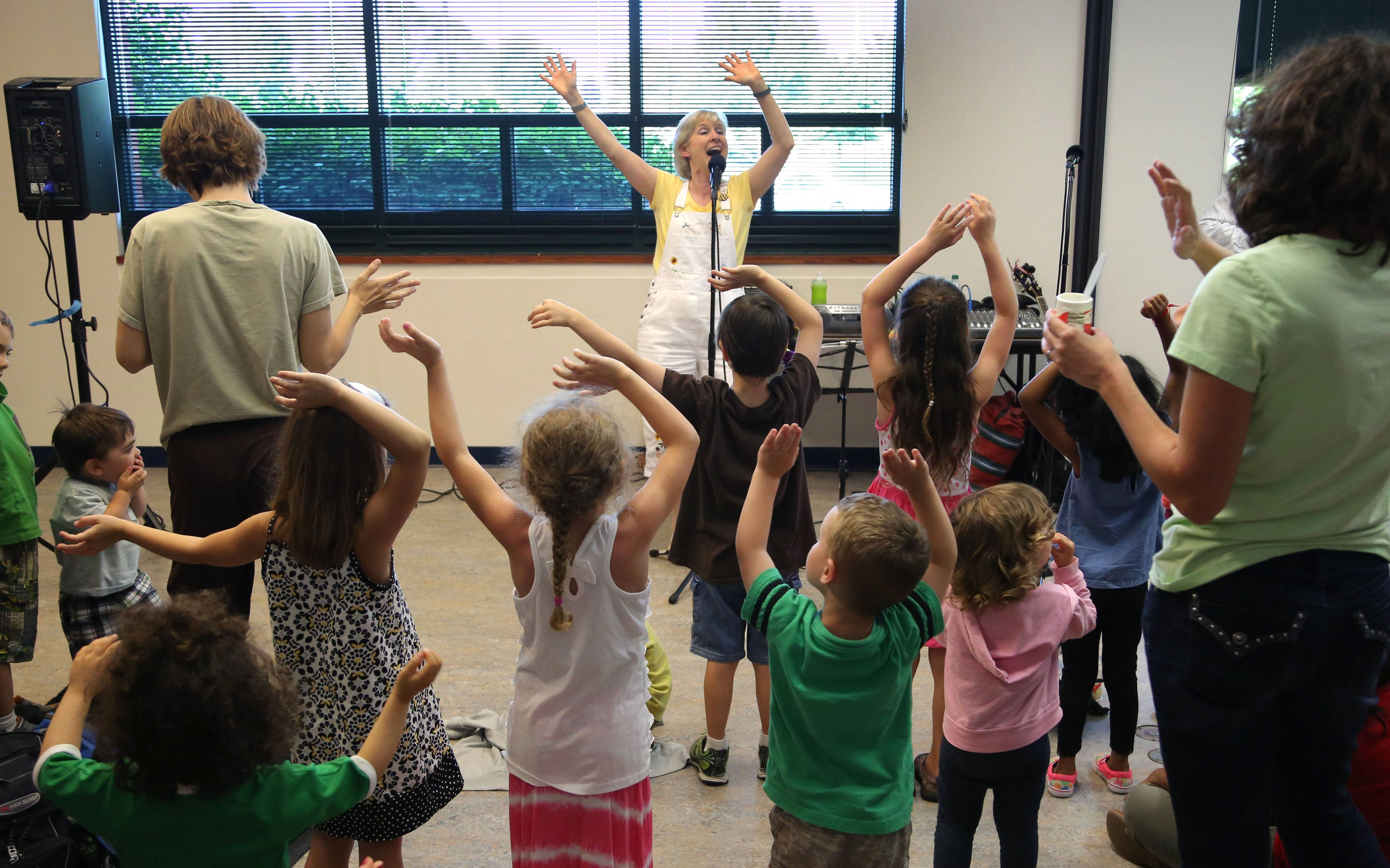 Carol Stephens of Park Ridge got kids to wiggle, giggle, hop and stomp as she brought her sing a long music and movement activities to the Grayslake Public Library Wednesday night.