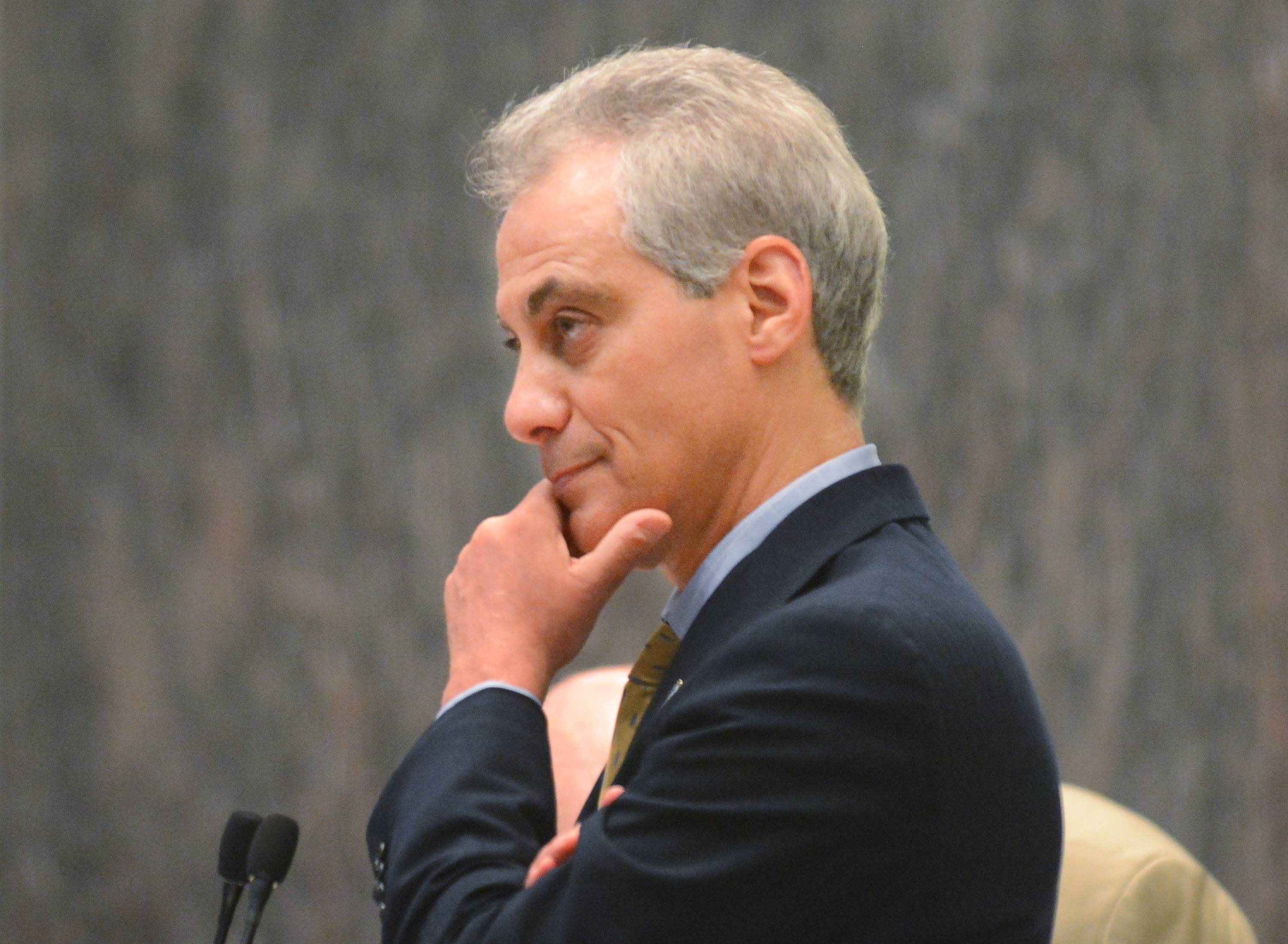 Chicago Mayor Rahm Emanuel listens during a city council meeting Wednesday During the meeting, the council approved an ordinance that dramatically limits where gun stores can operate and requires them to videotape every purchase to prevent one person from buying a gun for another.