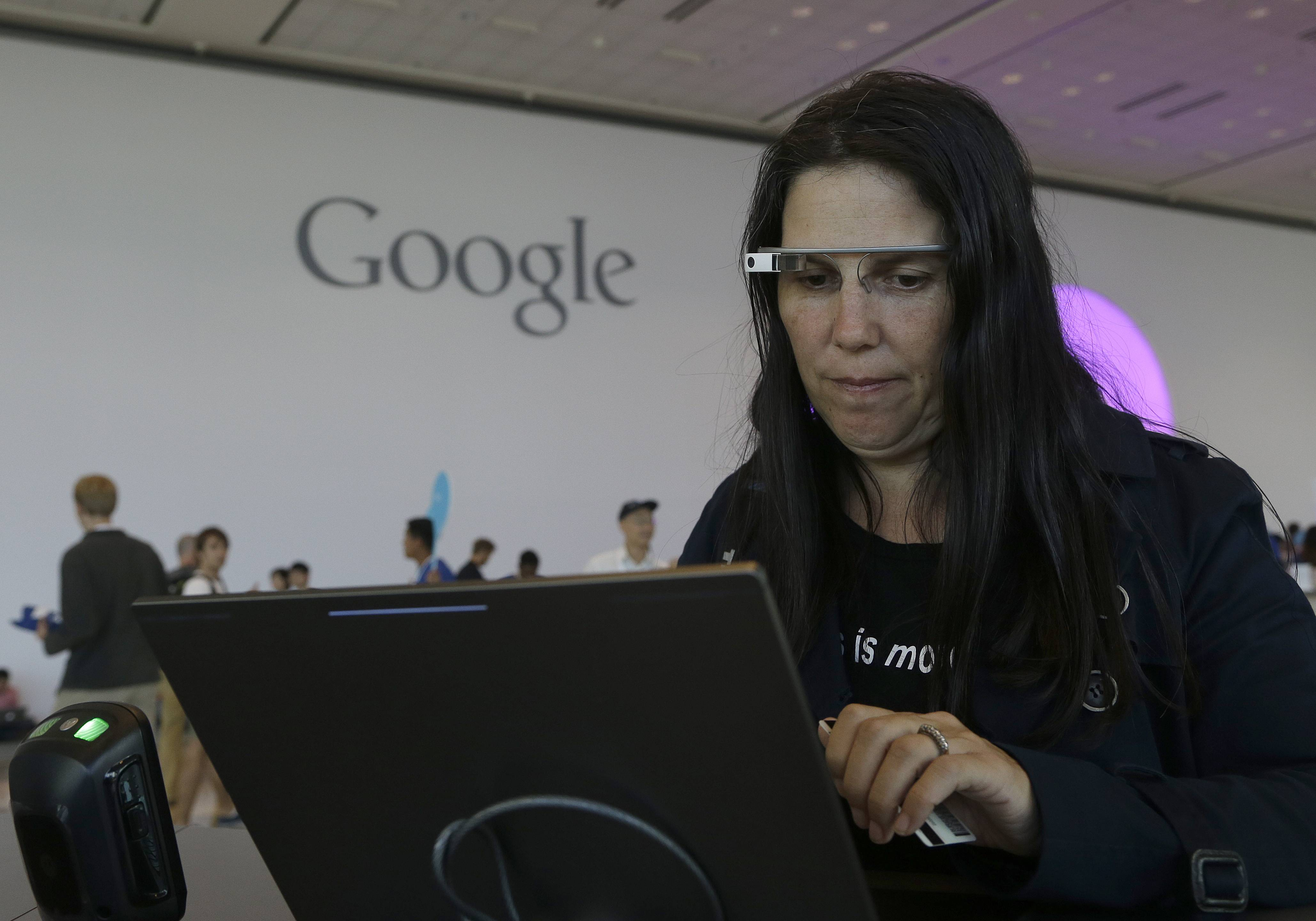 Cecilia Abadie, founder of 33 Labs, uses a pair of Google Glass as she registers for Google I/O 2014 at the Moscone Center in San Francisco, Tuesday, June 24, 2014.