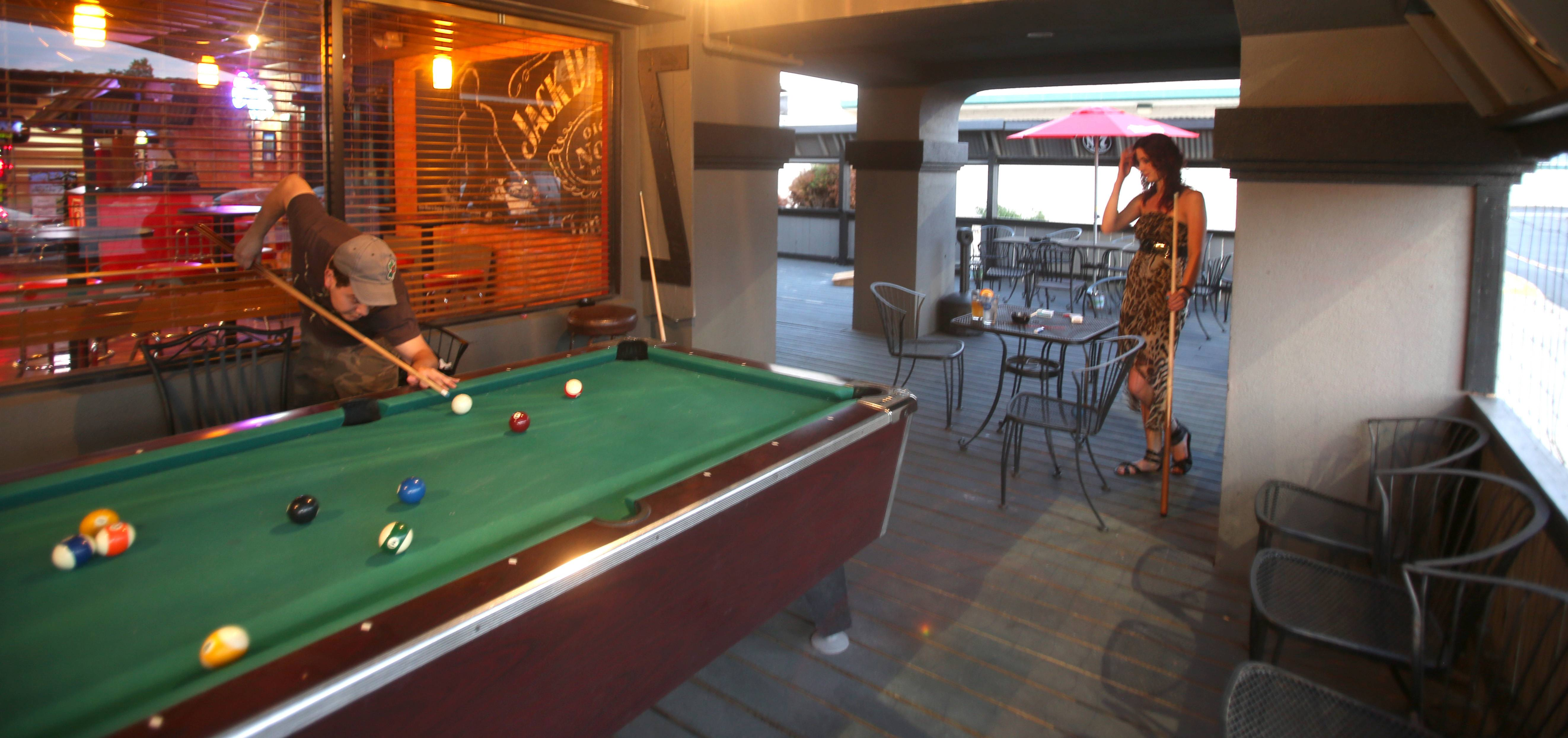 An outdoor pool table at Gnarly J's in Downers Grove attracts Eddie Torres and Jelena Lukic, both of Elk Grove Village.