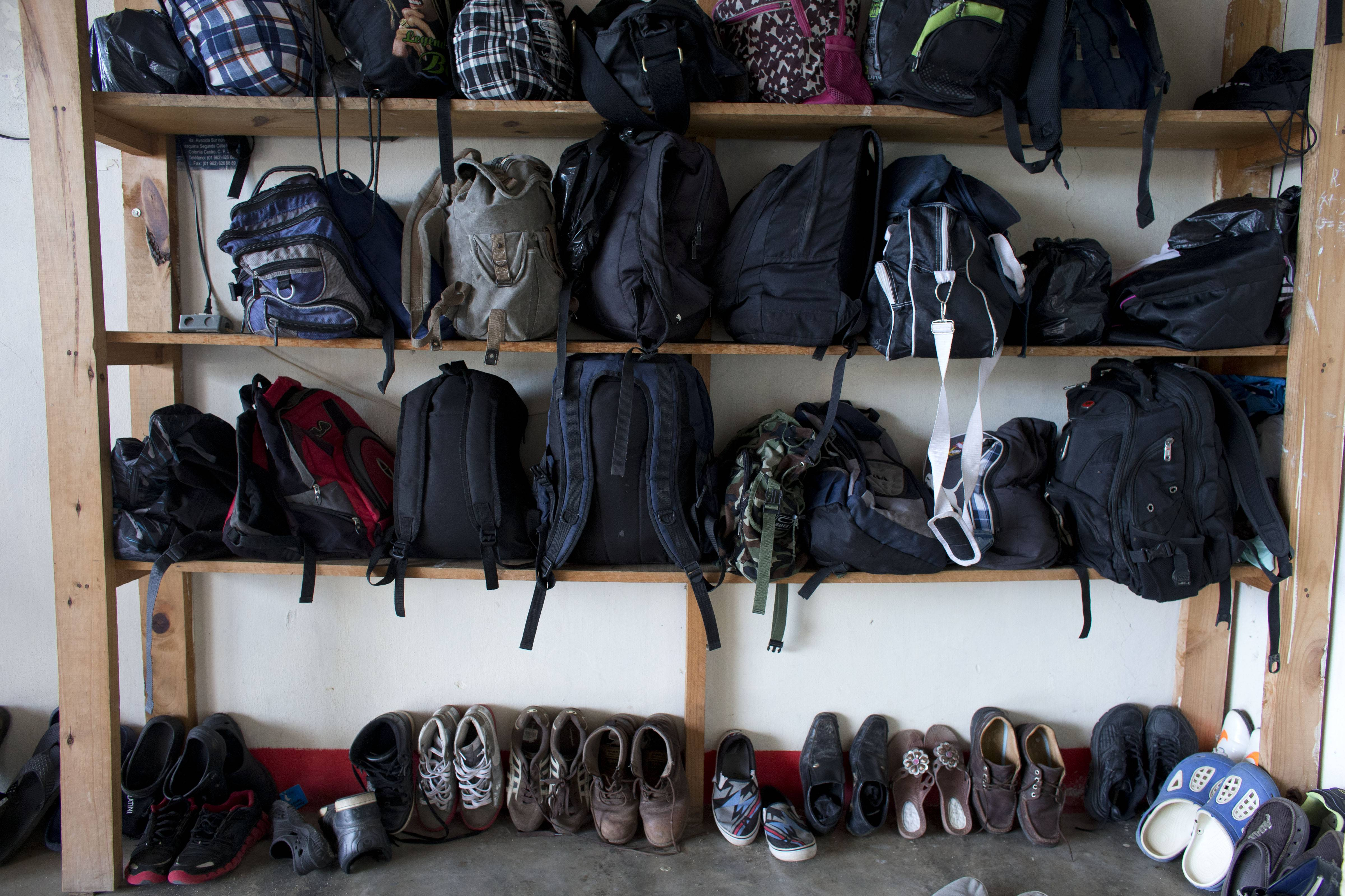 Migrants' bags and shoes line the edge of the room in the men's section of a shelter providing temporary refuge to Central Americans traveling north toward the U.S., in Arriaga, Chiapas State, Mexico. Most migrants travel with little more than a small backpack, permitting them to jump on and off trains more easily, and the best walking shoes they can afford.