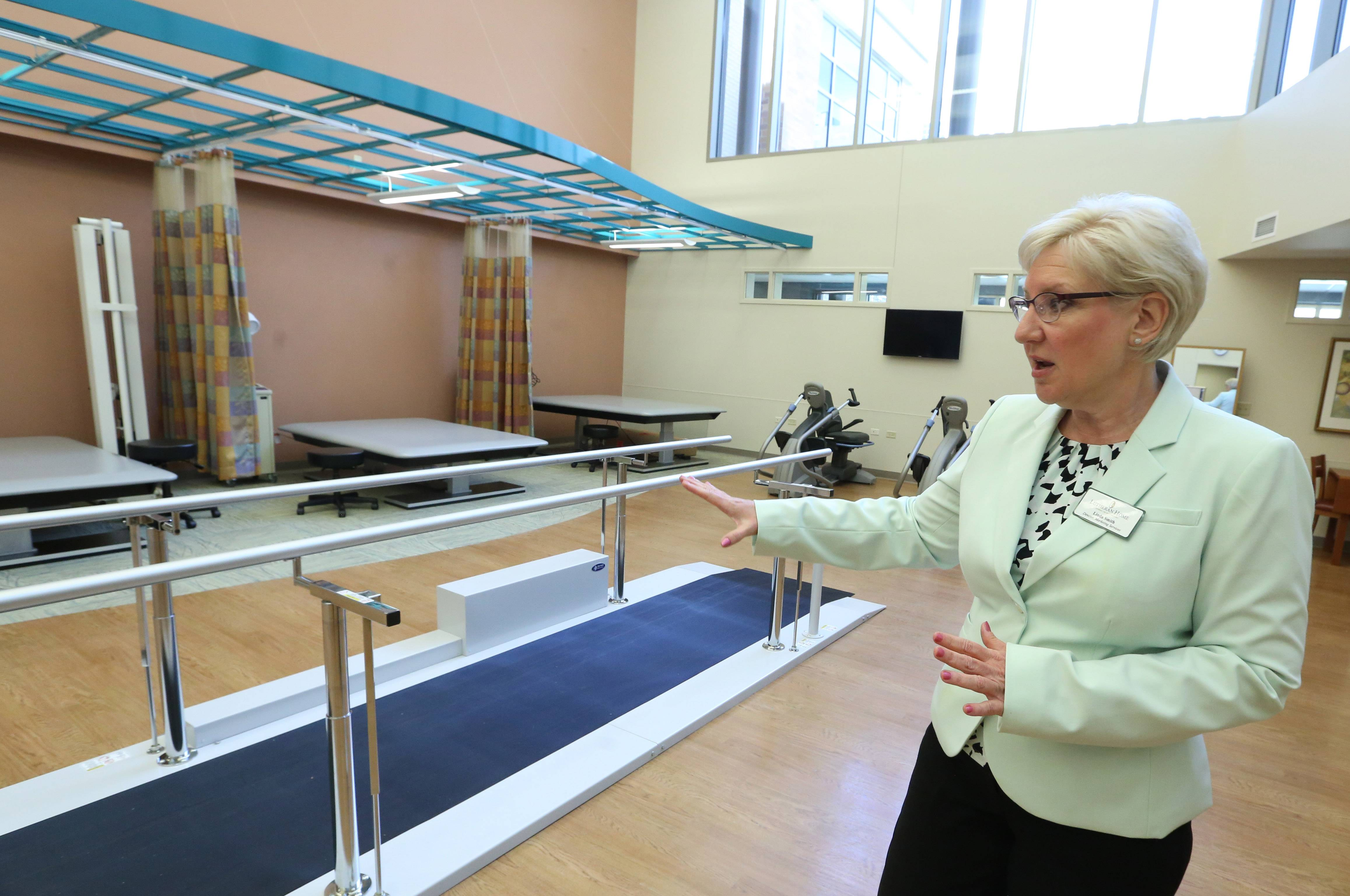 Linda Smith, director of marketing services for Lutheran Home, shows a rehabilitation room at Lutheran Home's new MyRehab Center in Arlington Heights. The center geared toward short-term rehabilitation patients is the first of a three-part, $64 million project to modernize and renovate Lutheran Home.
