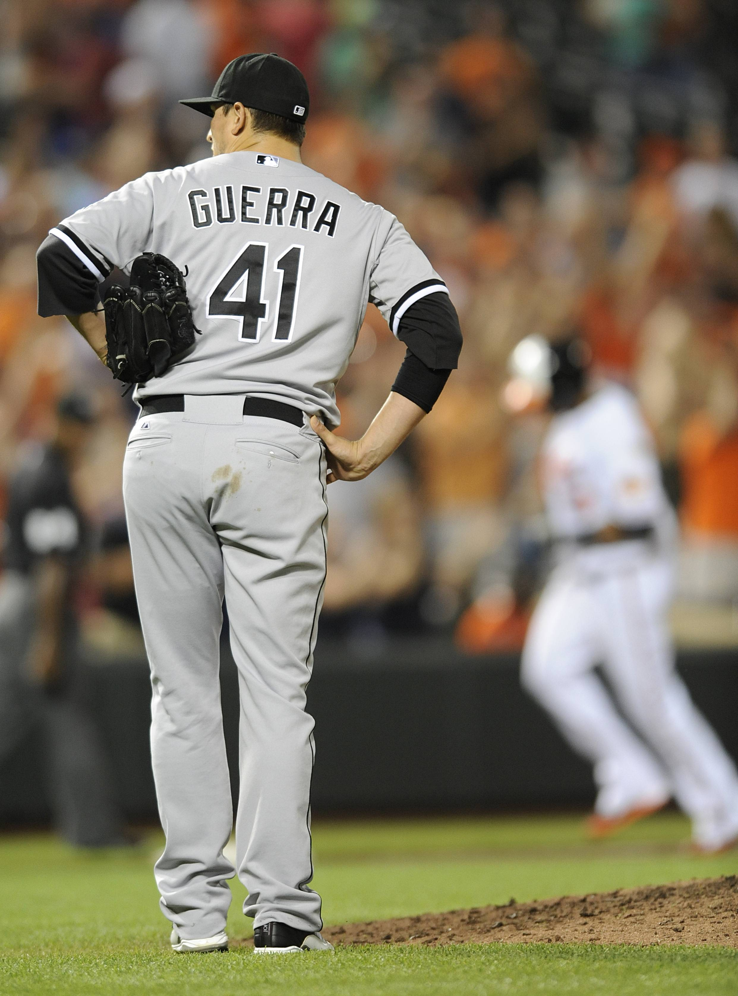 White Sox pitcher Javy Guerra pauses in front of the mound after giving up a grand slam to Baltimore Orioles' Nelson Cruz, at right, to tie the game in the eighth inning, Wednesday. The Sox went on to lose 5-4 in the 12th.