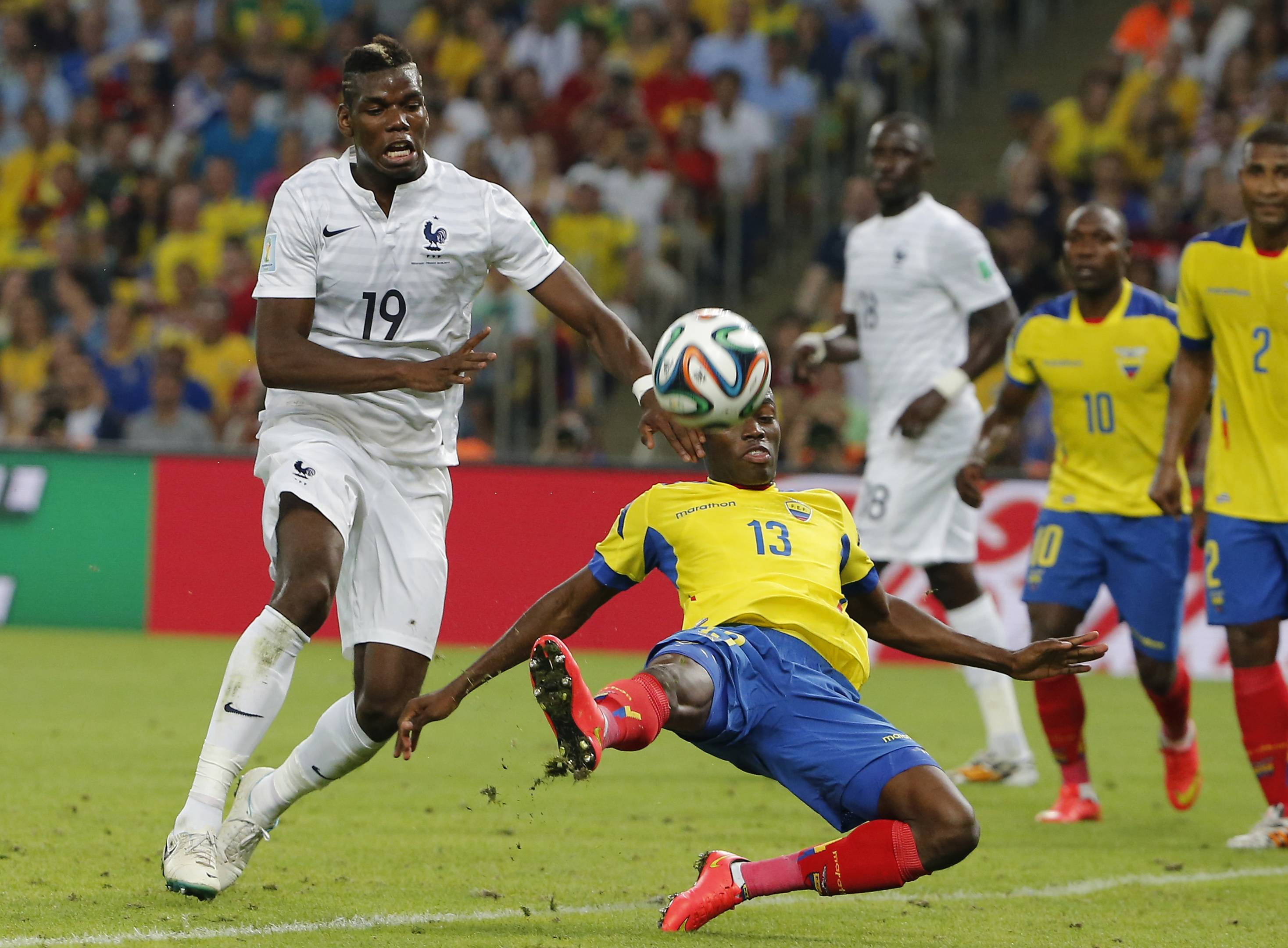Ecuador's Enner Valencia, bottom, and France's Paul Pogba challenge for the ball during the group E World Cup soccer match between Ecuador and France at the Maracana stadium in Rio de Janeiro, Brazil, Wednesday, June 25, 2014.