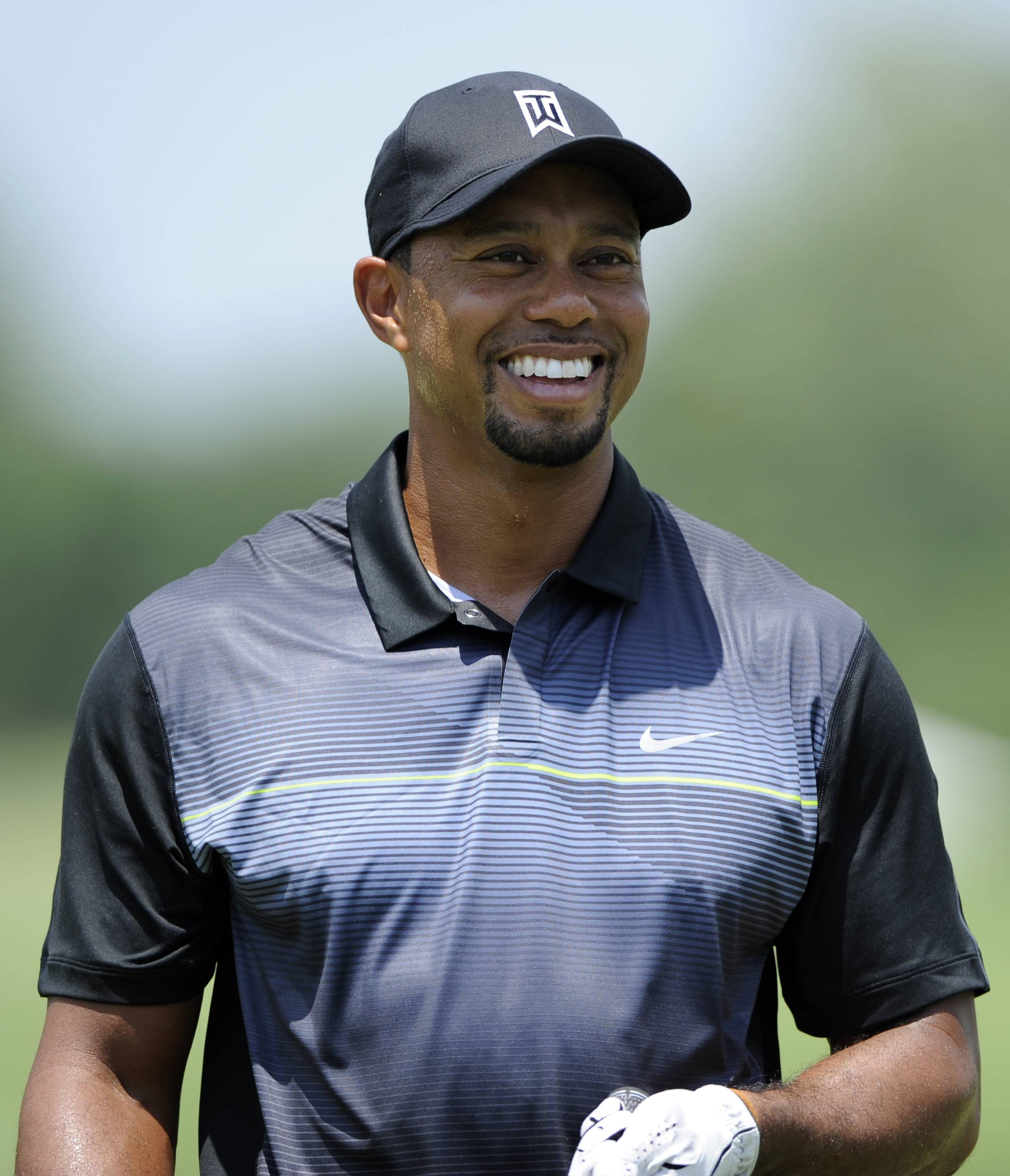 After a good practice round and more work at the driving ranger, Tiger Woods emerged with a smile as he prepared for the Quicken Loans National golf tournament.