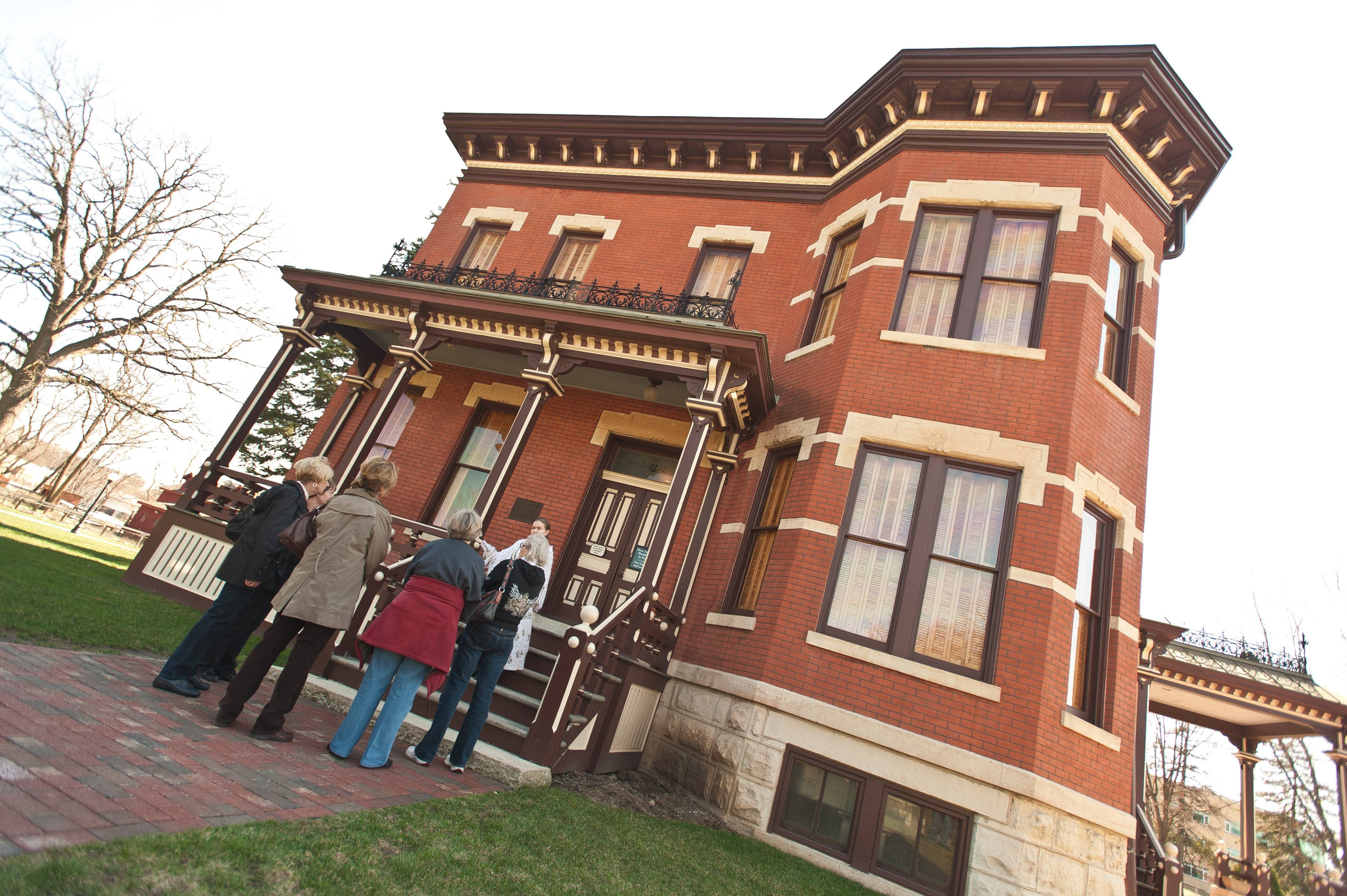 Naper Settlement volunteer Avery Sipla gives a tour of the Martin Mitchell Mansion, which is celebrating its 130th anniversary in 2014.