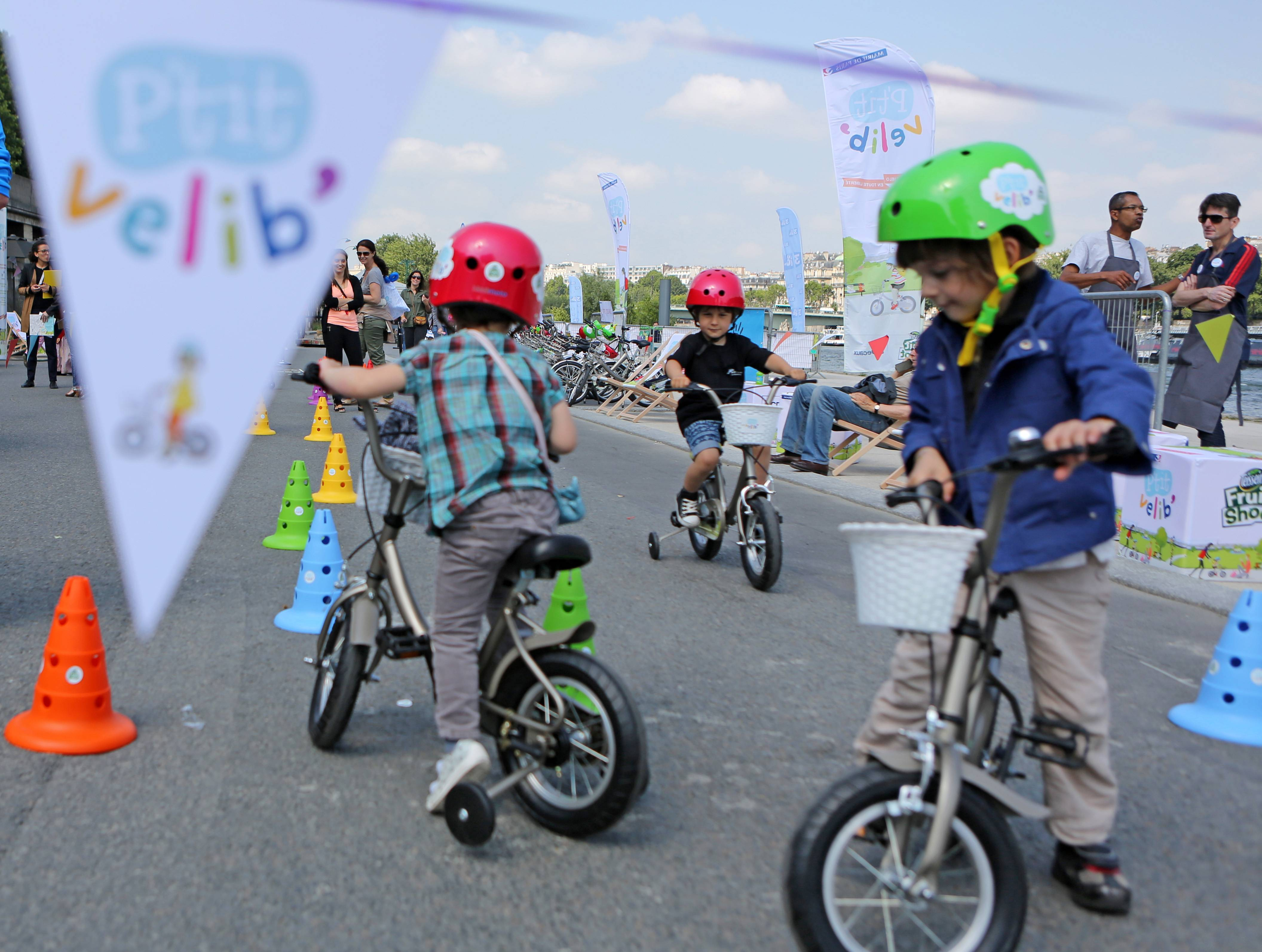 Children ride free bicycles as part of the Little Velib system experiment on the Seine river banks in Paris.