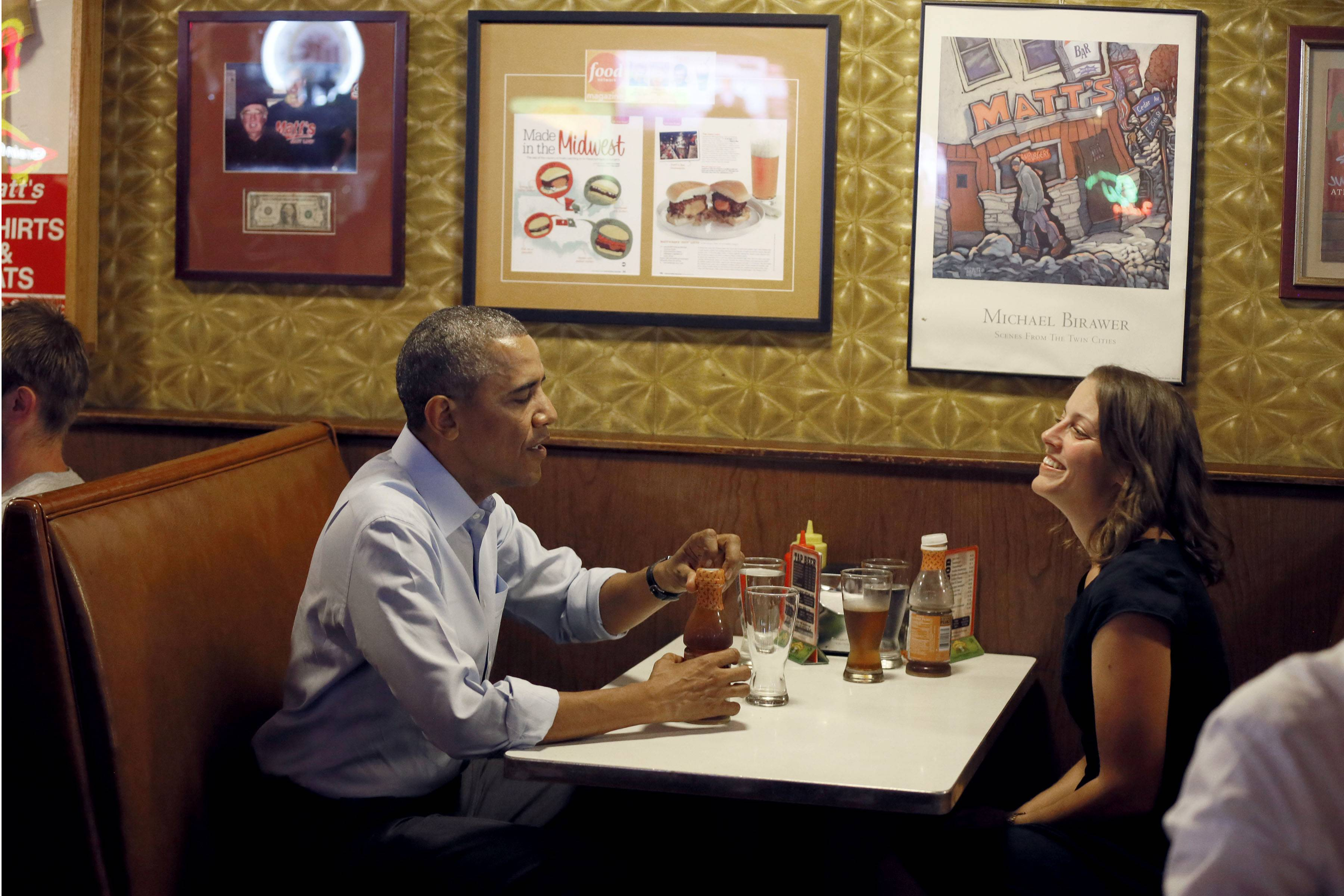 President Barack Obama talks with Rebekah Erler, of Minneapolis, at Matts Bar before going to a town hall meeting in Minneapolis Thursday. The president was in town for the first in a series of day-in-the-Life visits he plans to make across the country this summer.