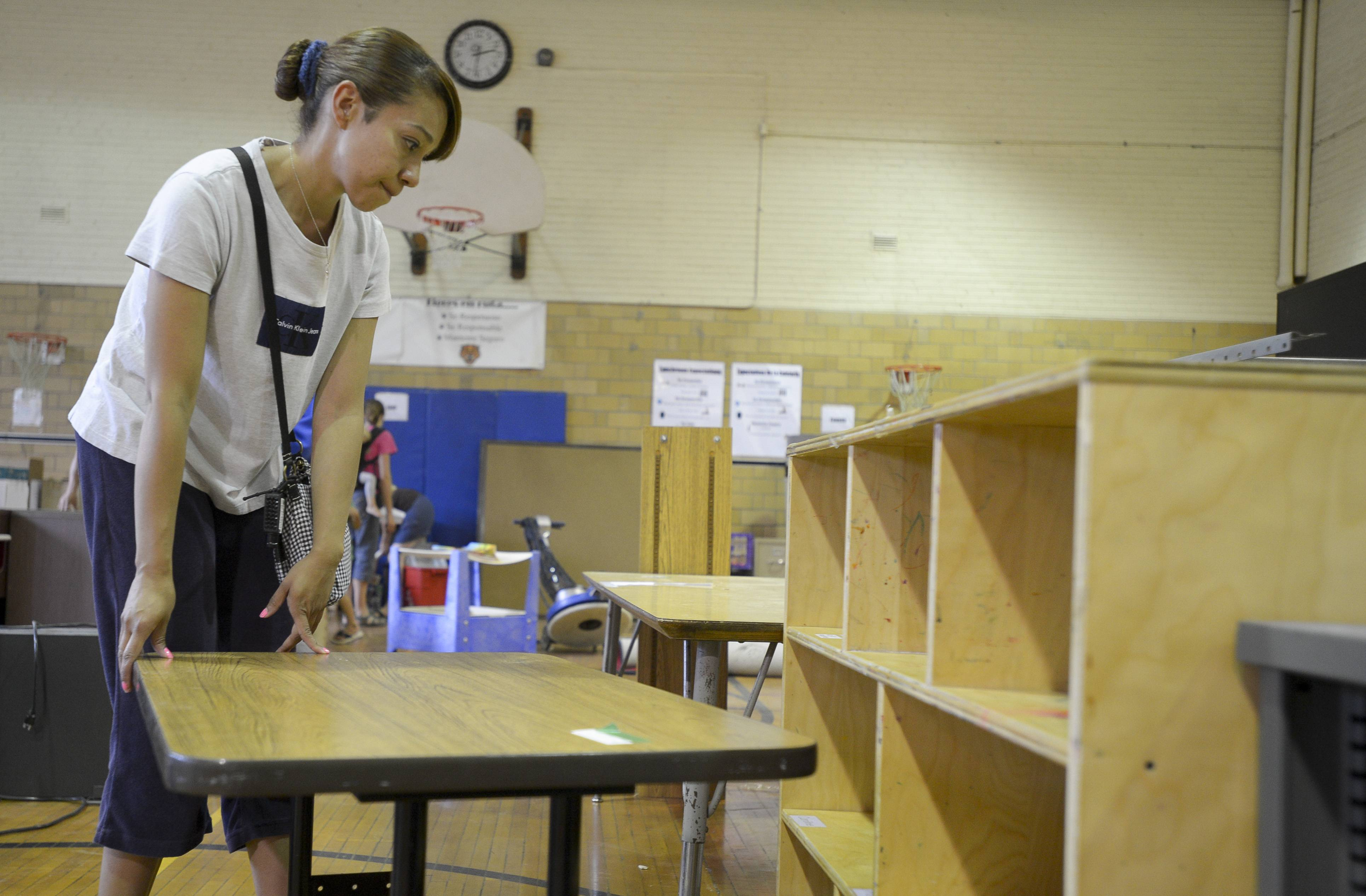 Visiting teacher Marlene Hernandez searches for items for her classroom at the Tioga Elementary School surplus sale, held Wednesday in the old gymnasium of the Bensenville school.
