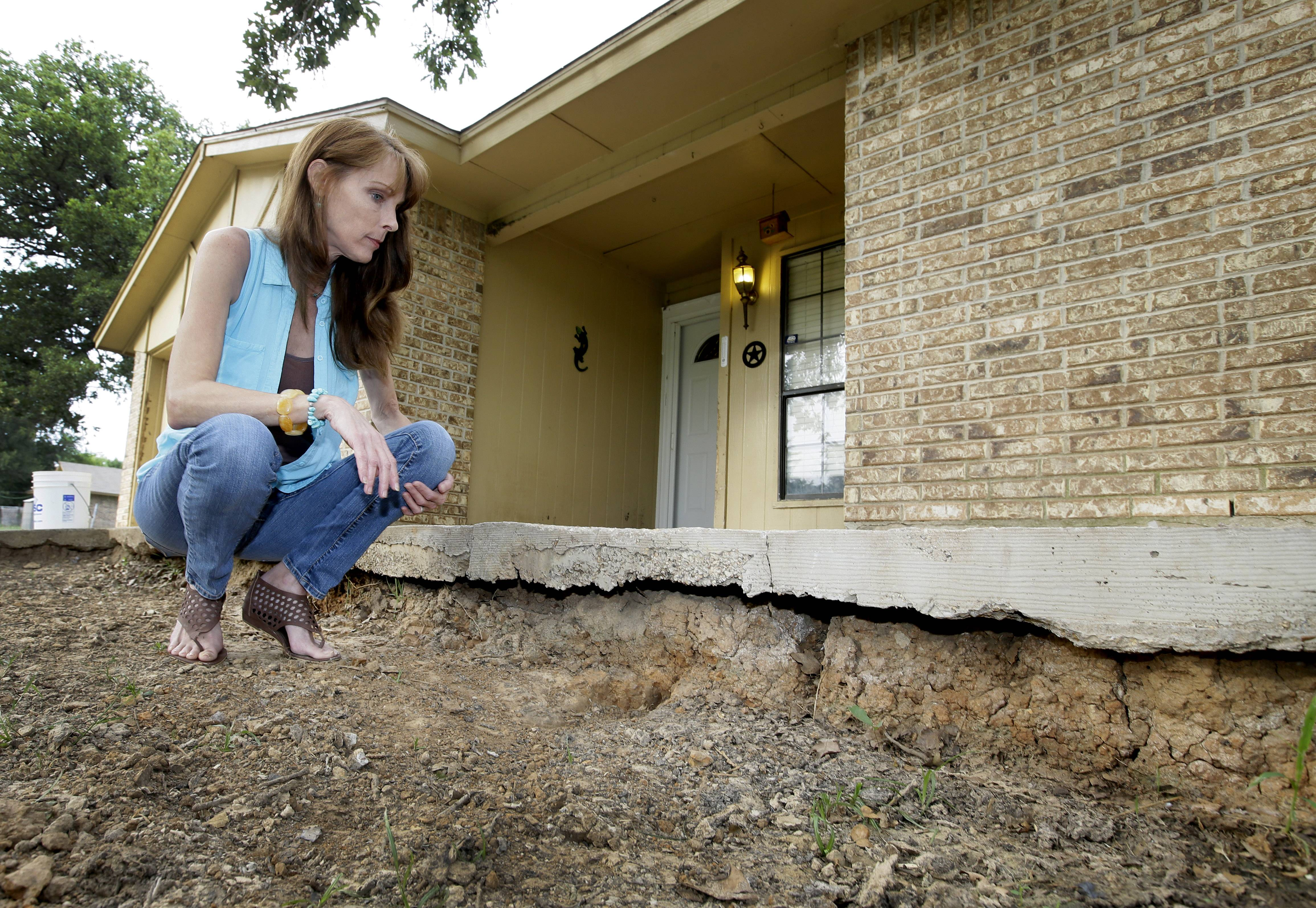 Barbara Brown poses for a photo by the front step of her home that now sits about one foot off the surface of her lawn, Saturday, June 21, 2014, in Reno, Texas. Brown said that the top of the step once sat about four inches off the surface of her lawn. Brown said she believes the sinkholes on her property and the drop of her lawn have to do with natural gas drilling.