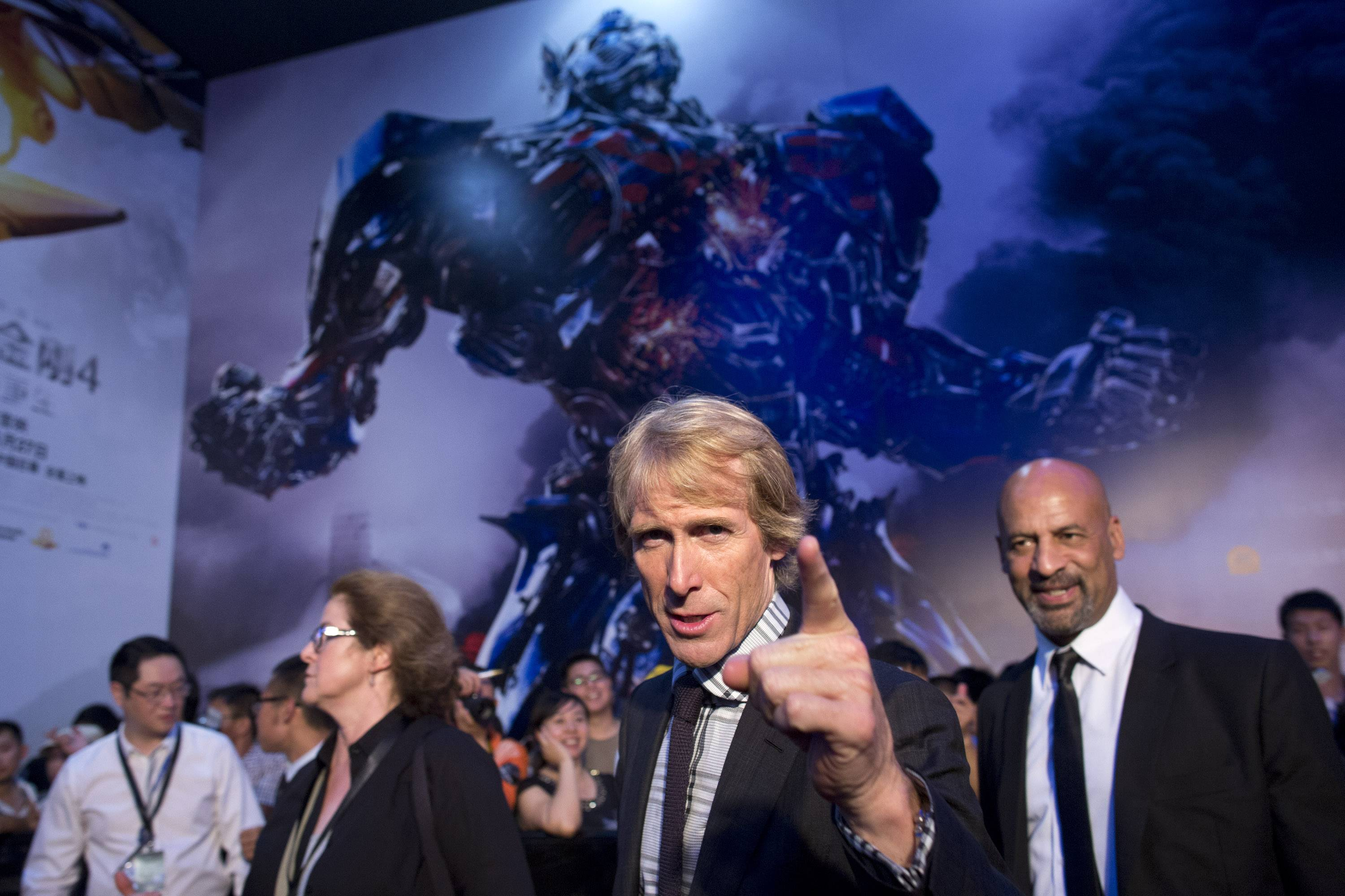 "Director Michael Bay, center, gestures to fans as he attends the premiere of movie ""Transformers: Age of Extinction"" at a theatre in Beijing, China."