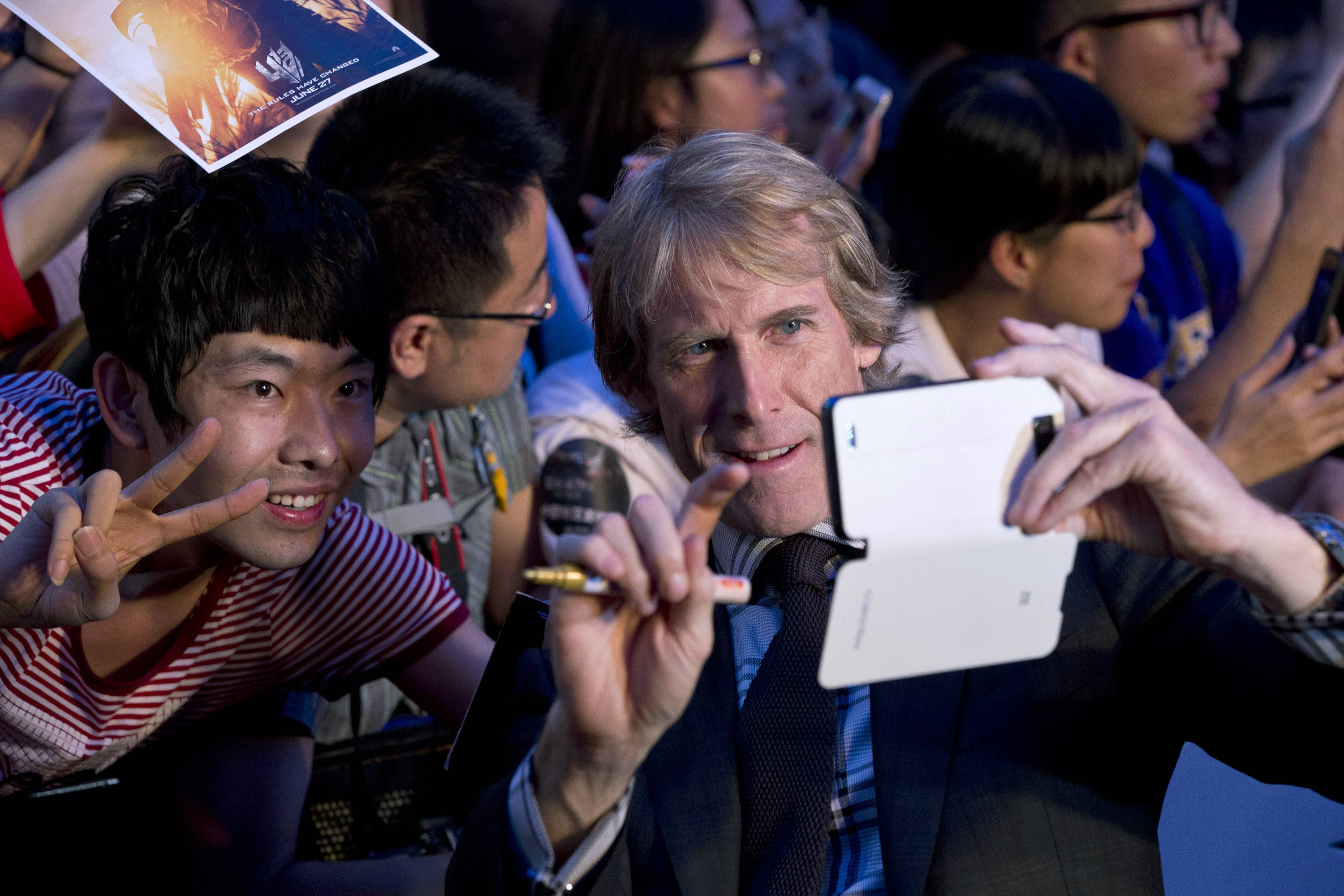 "Director Michael Bay, front right, takes mobile phone photos for a Chinese fan as he attends the premiere of movie ""Transformers: Age of Extinction"" at a theatre in Beijing, China."