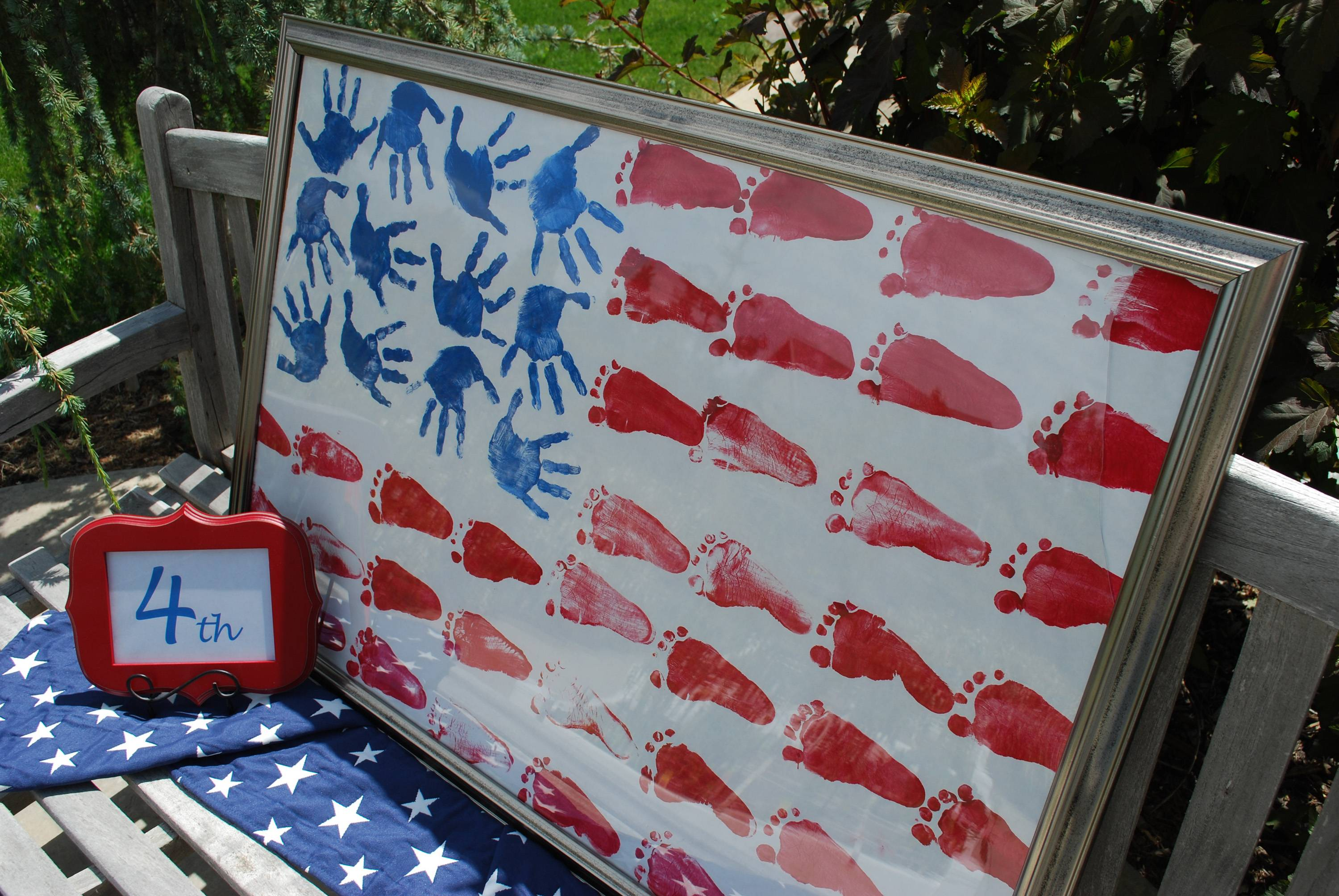 "To commemorate Independence Day, create a family memento in the shape of a flag out of kids' painted hands and feet: Hands provide blue ""stars"" and little feet stamp out red stripes in acrylic paint on white craft paper."