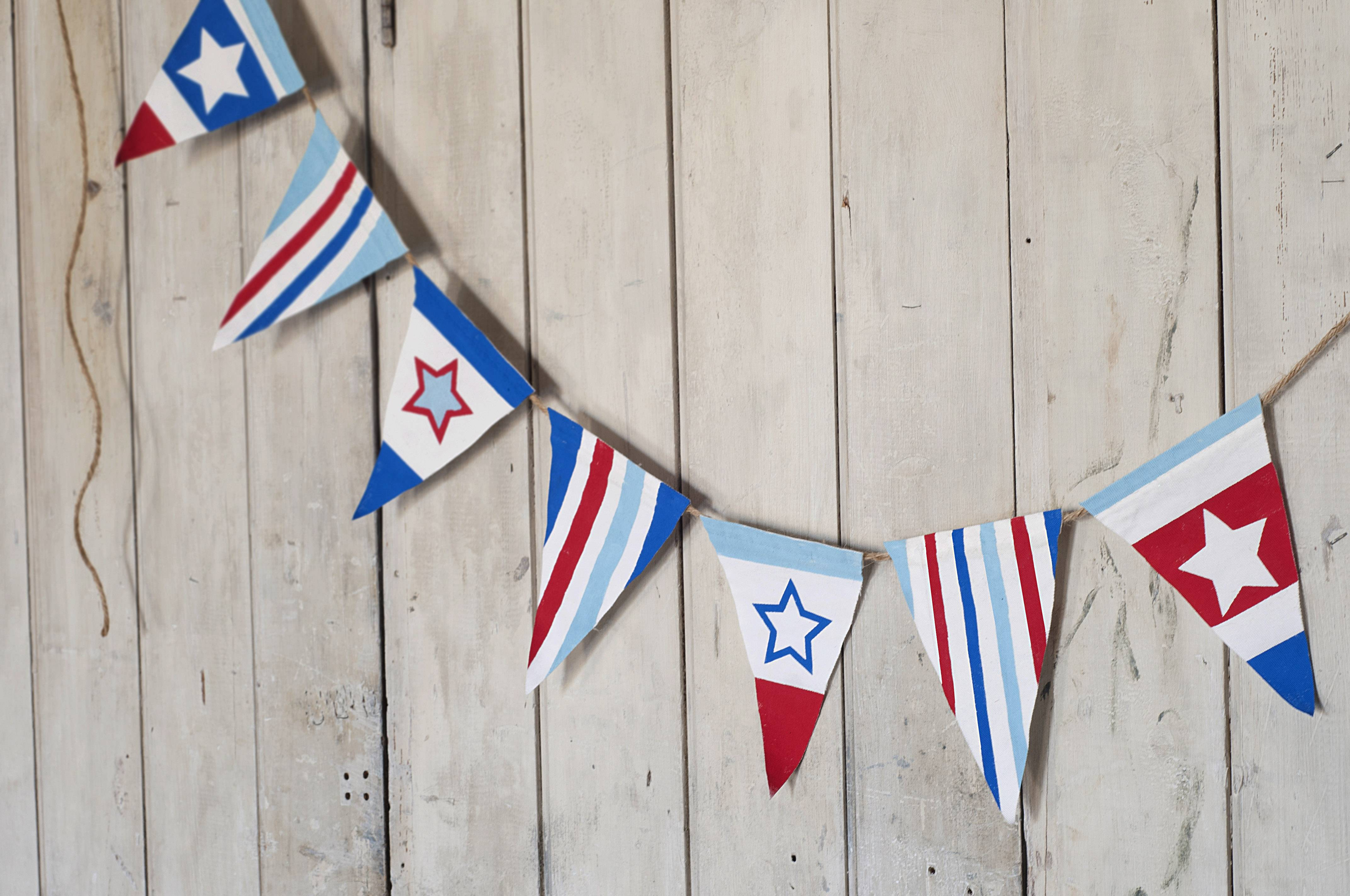 Stars and Stripes Bunting can be a fun craft for kids to make for Independence Day. The essential supplies include fabric or paper, freezer paper and acrylic paint.