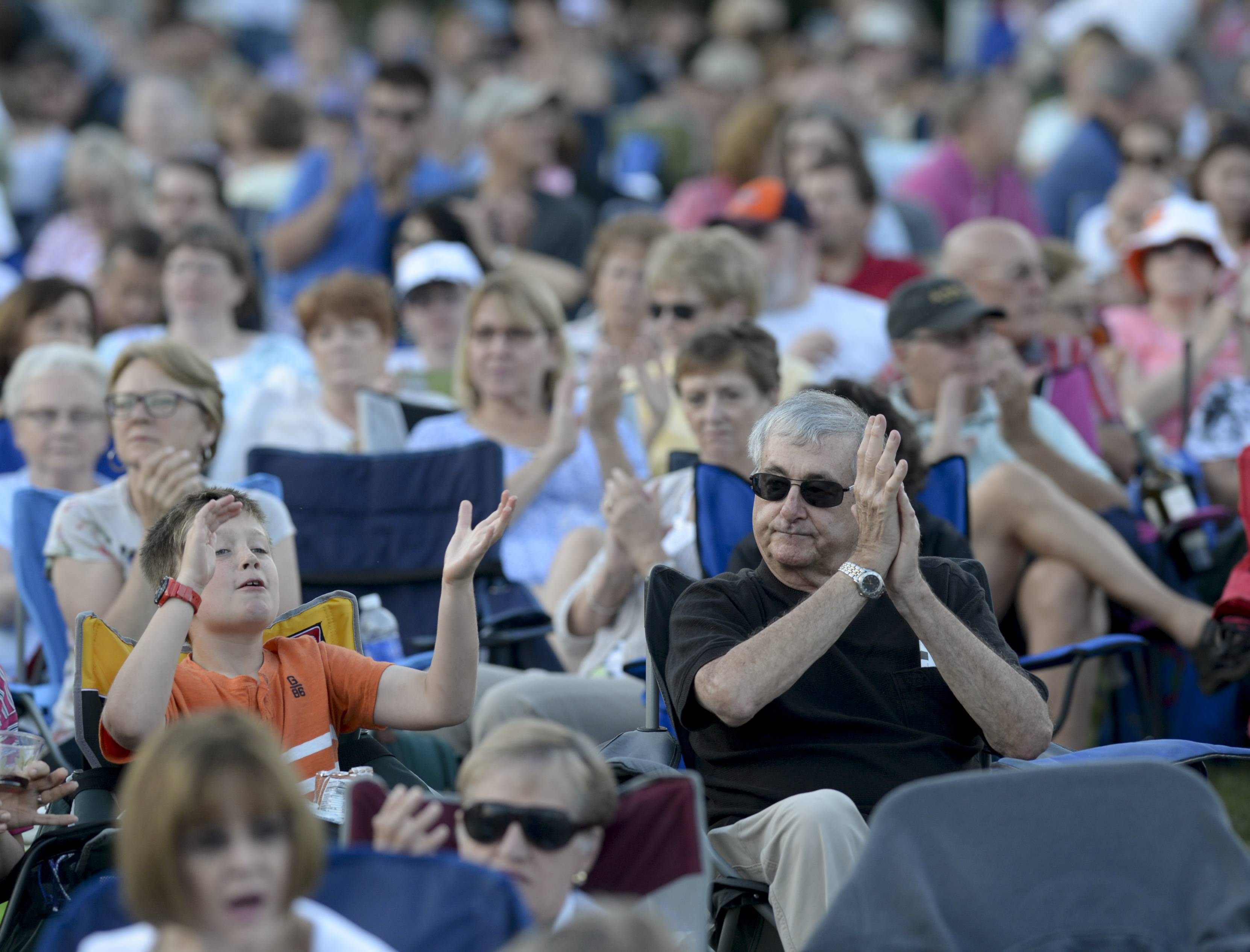 Mark Black/mblack@dailyherald.comLuke Wagner, 9 and his grandfather Leonard Spencer both of Naperville applaud during the Chicago Symphony Orchestra's performance Thursday night at The Morton Arboretum in Lisle.