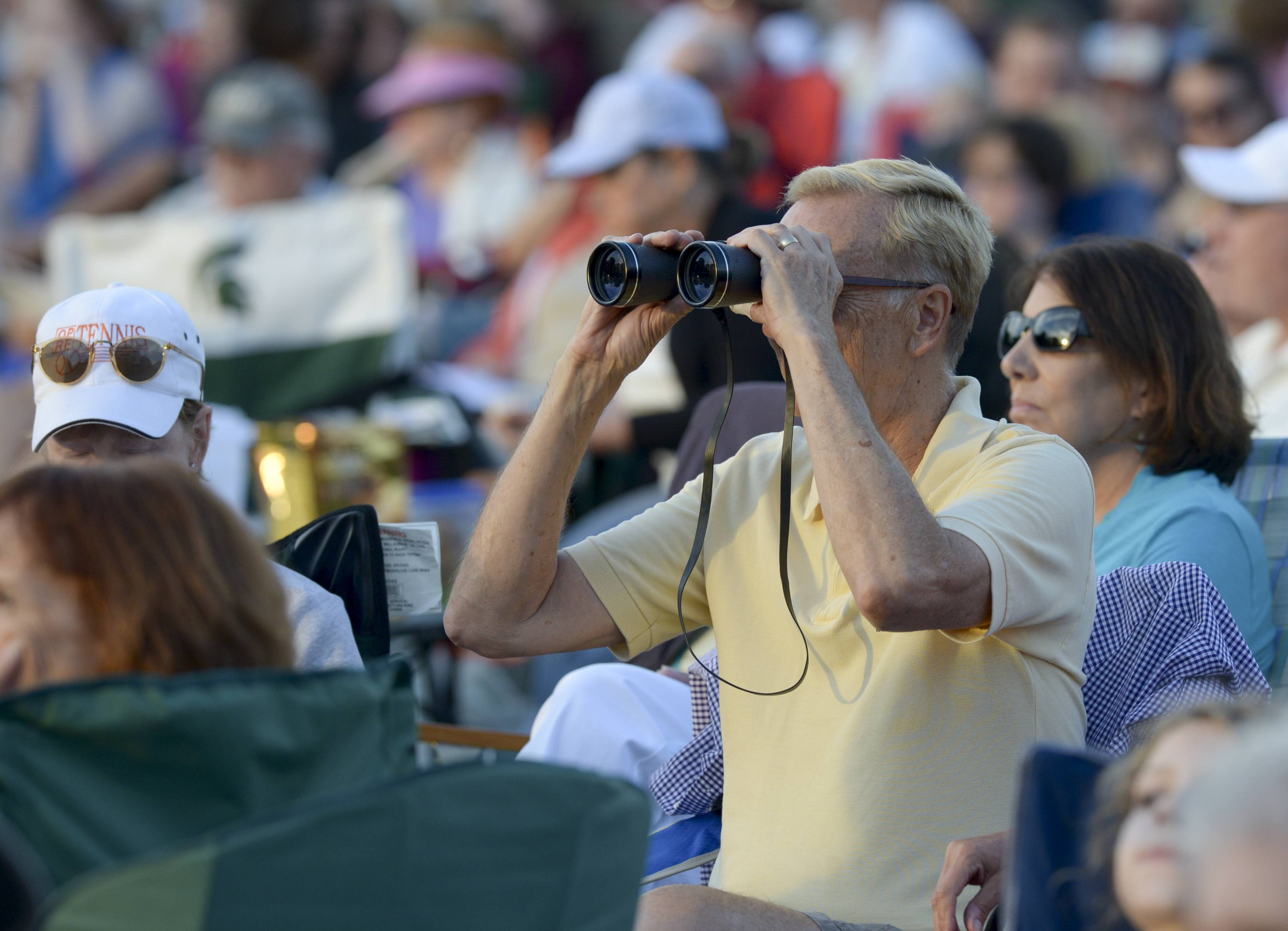 Mark Black/mblack@dailyherald.comTed Steiskal of Hillside uses a pair of binoculars to get a closer look while attending the Chicago Symphony Orchestra's performance Thursday night at The Morton Arboretum in Lisle.