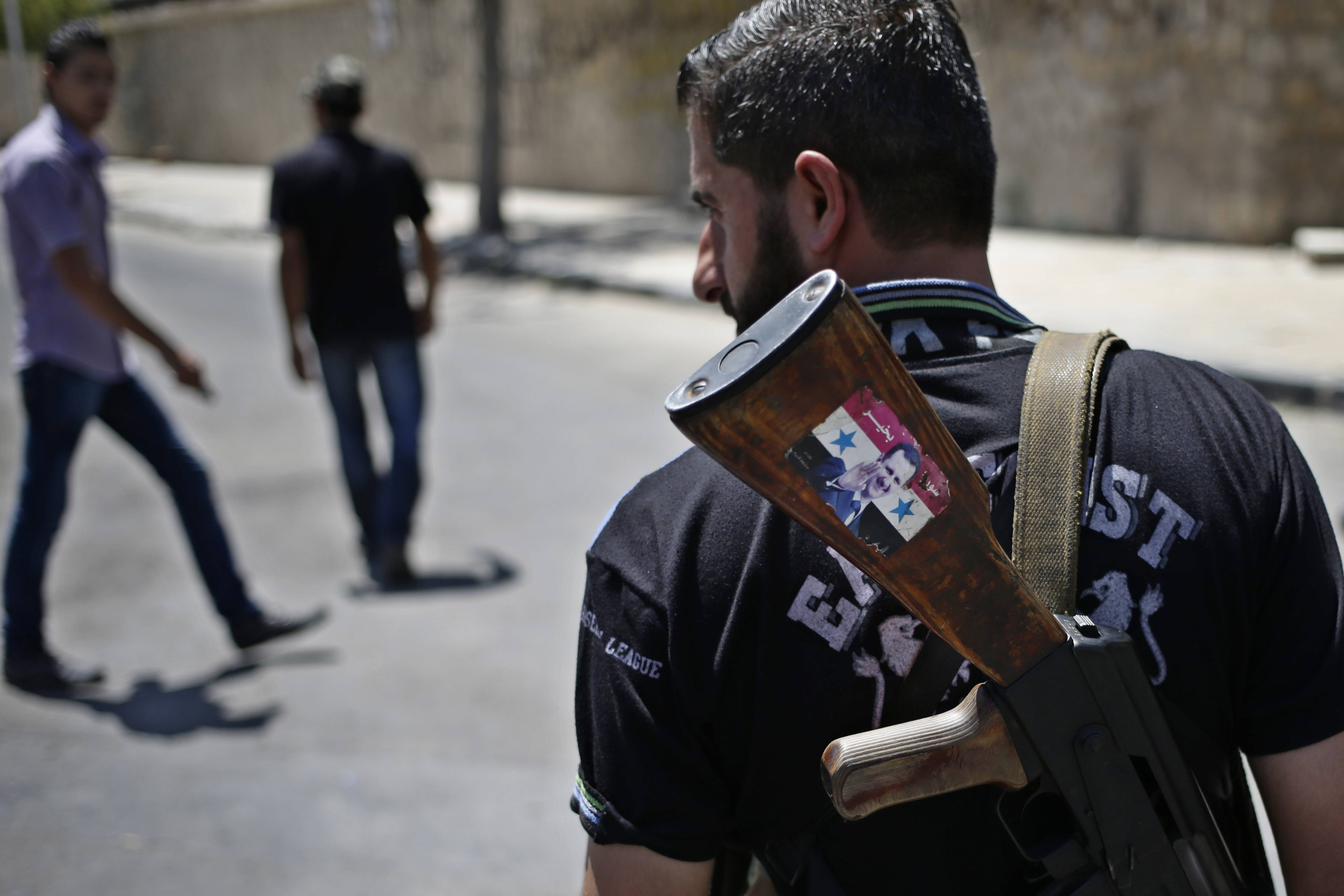 "A Syrian military soldier holding his AK-47 with a sticker of Syrian President Bashar Assad and Arabic that reads, ""Syria is fine,"" as he stands guard at a check point in Damascus, Syria. President Barack Obama is asking Congress for $500 million to train and arm vetted members of the Syrian opposition."