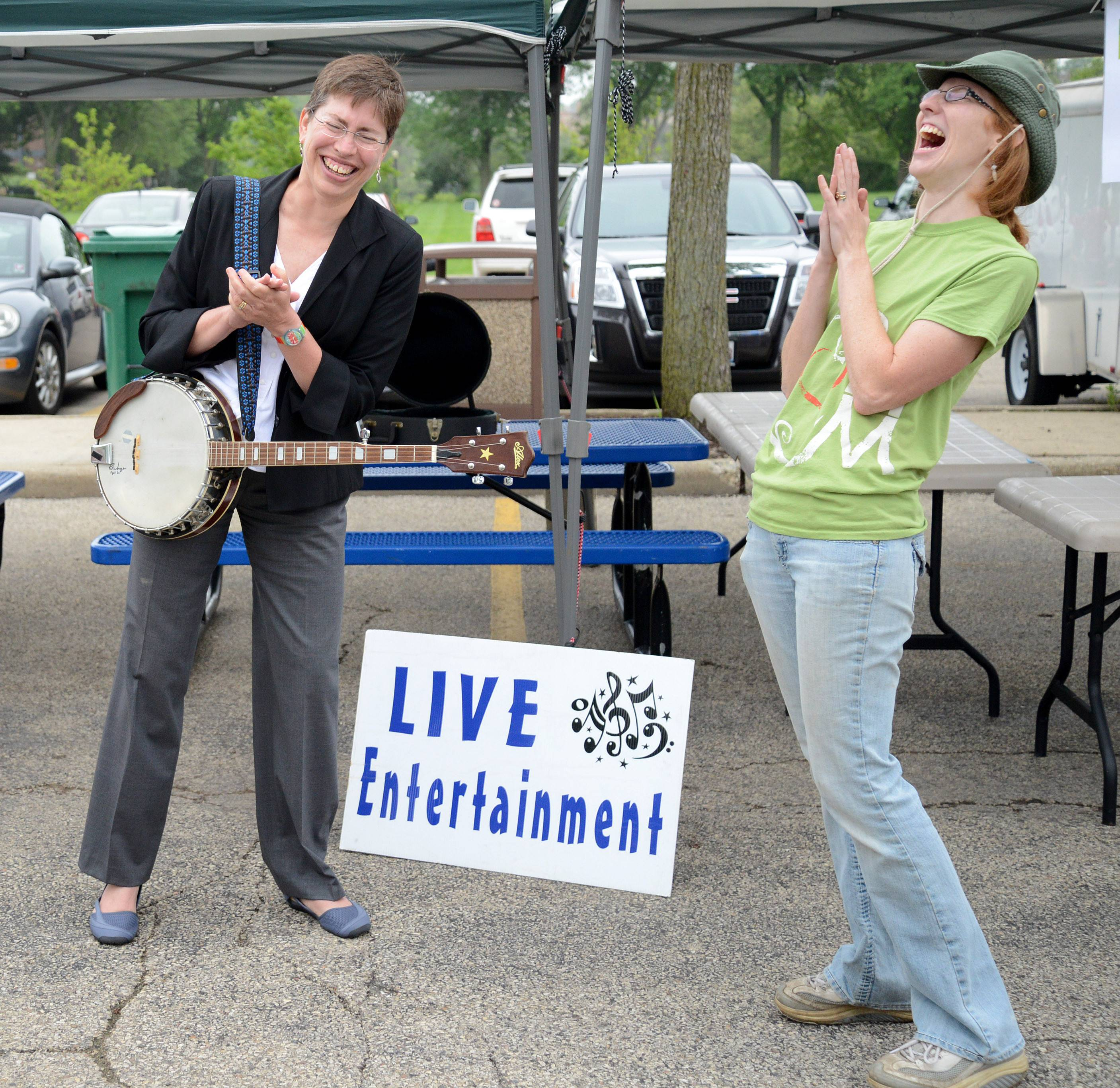 "Lt. Gov. Sheila Simon, left, and Downtown Elgin Harvest Market manger Jennifer Benson complete a singalong to ""Down by the Riverside"" during Simon's impromptu banjo concert at the market Thursday."