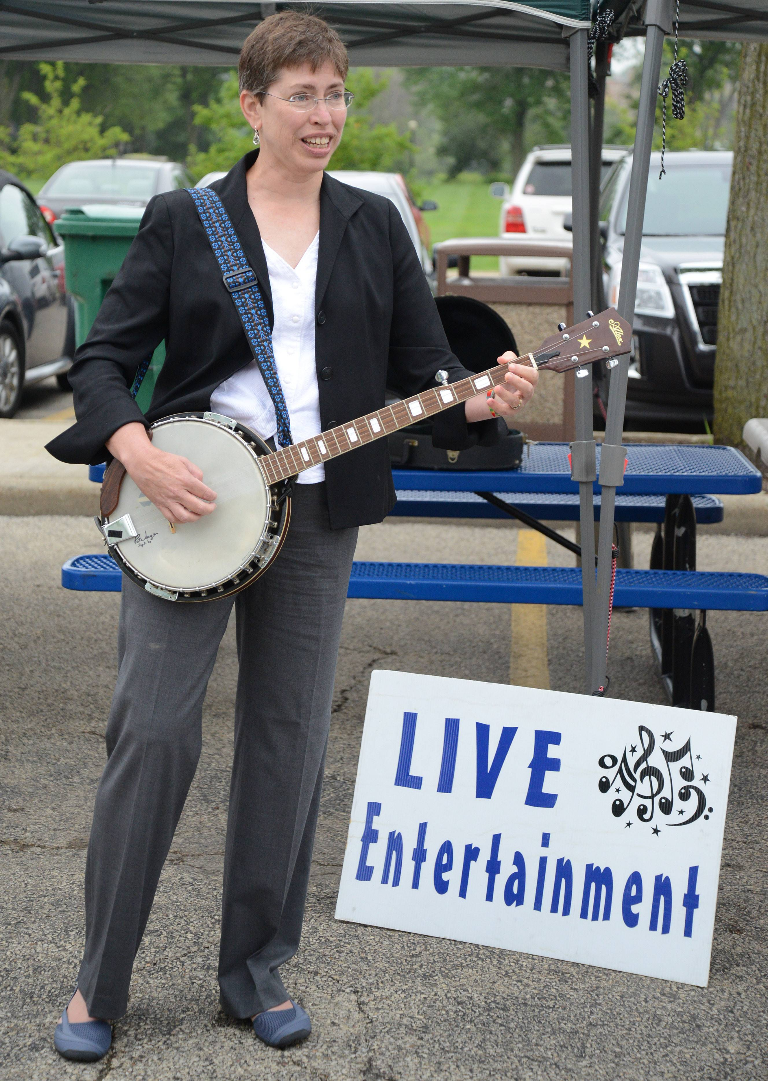 Lt. Gov. Sheila Simon gives an impromptu banjo concert at the Downtown Elgin Harvest Market Thursday. Simon was there advocating for locally grown food and urging more markets to accept Link cards.
