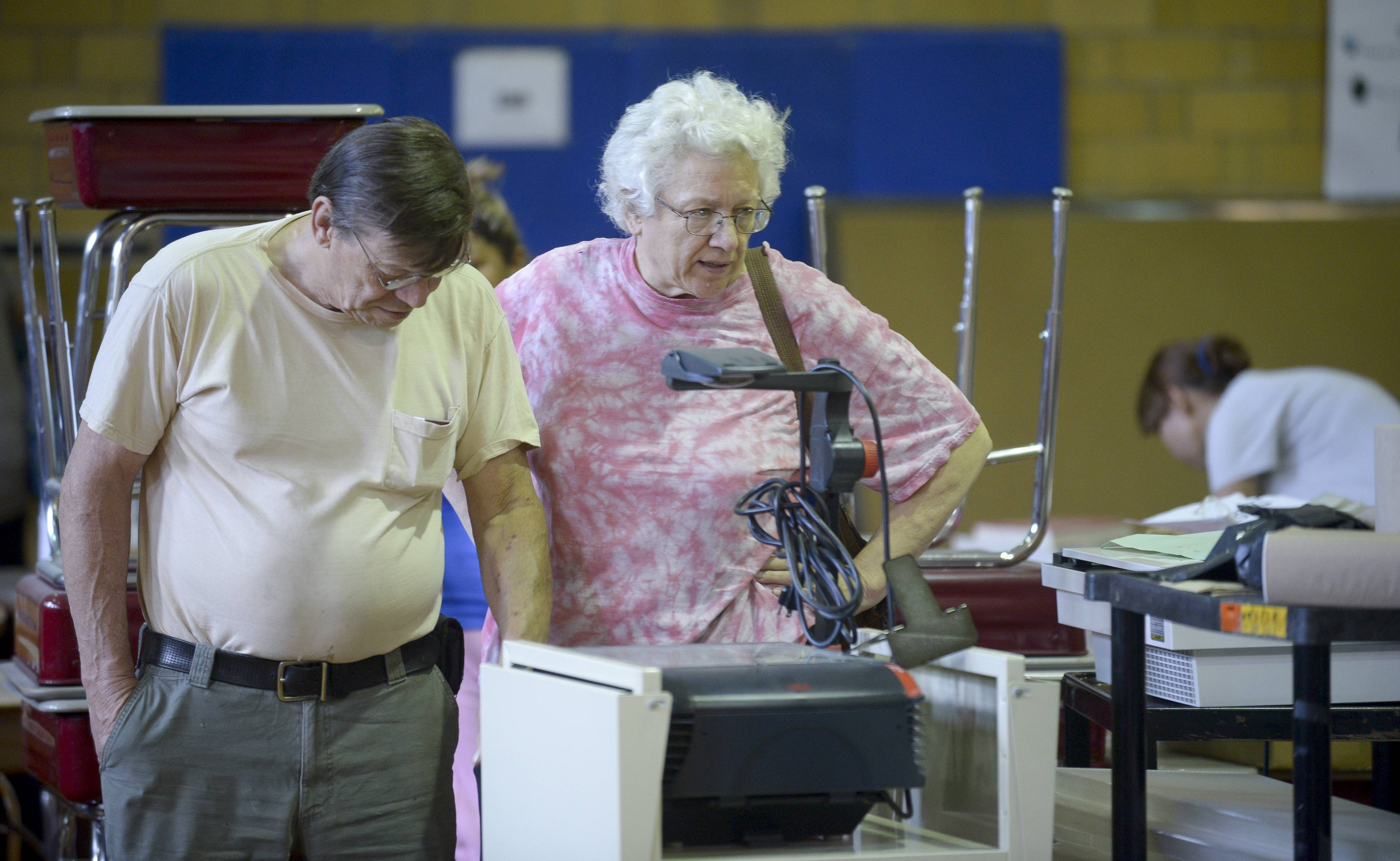Jim and Linda Topel of Bensenville check out an overhead projector at the Tioga Elementary School surplus sale, held in the school's old gymnasium.