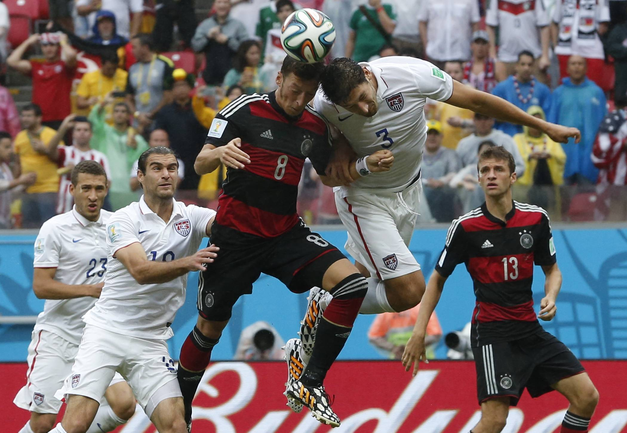 Germany's Mesut Ozil, center, goes for a header with United States' Omar Gonzalez as United States' Graham Zusi, left, looks on during the group G World Cup soccer match between the USA and Germany at the Arena Pernambuco in Recife, Brazil, Thursday, June 26, 2014.