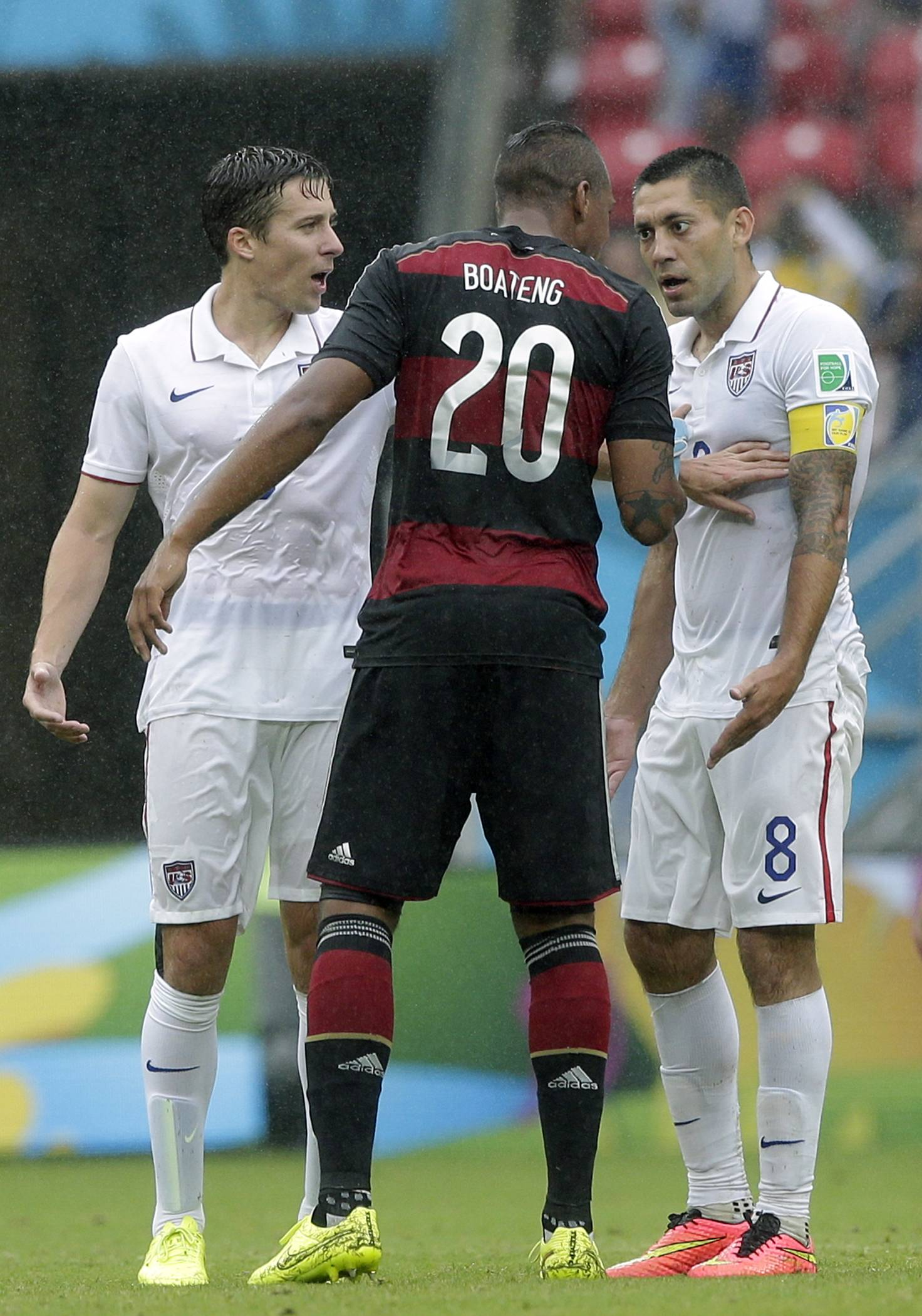 Germany's Jerome Boateng, center, argues with United States' Clint Dempsey, right, as United States' Omar Gonzalez looks on during the group G World Cup soccer match between the USA and Germany at the Arena Pernambuco in Recife, Brazil, Thursday, June 26, 2014.