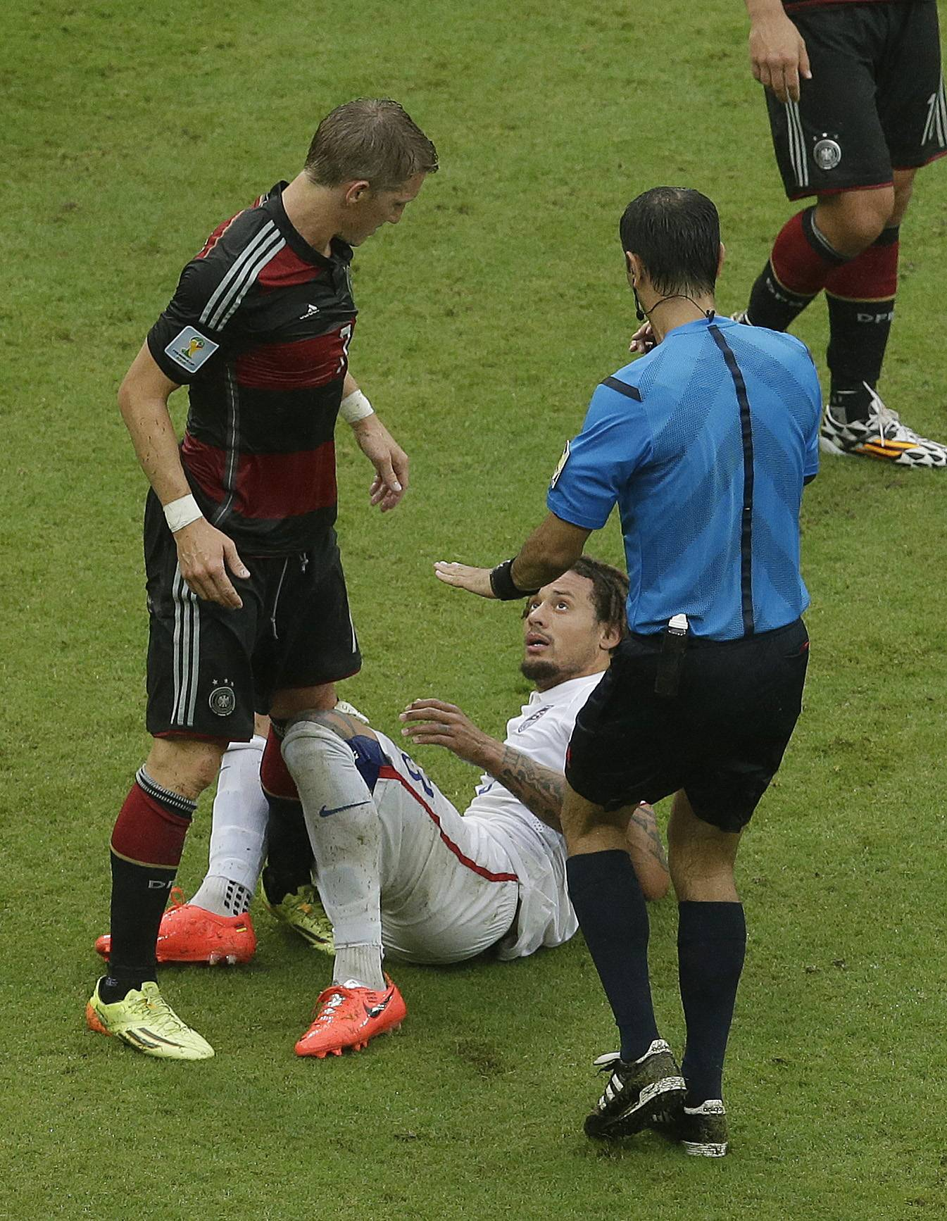 The referee warns United States' Jermaine Jones after a collision with Germany's Bastian Schweinsteiger, left, during the group G World Cup soccer match between the USA and Germany at the Arena Pernambuco in Recife, Brazil, Thursday, June 26, 2014.